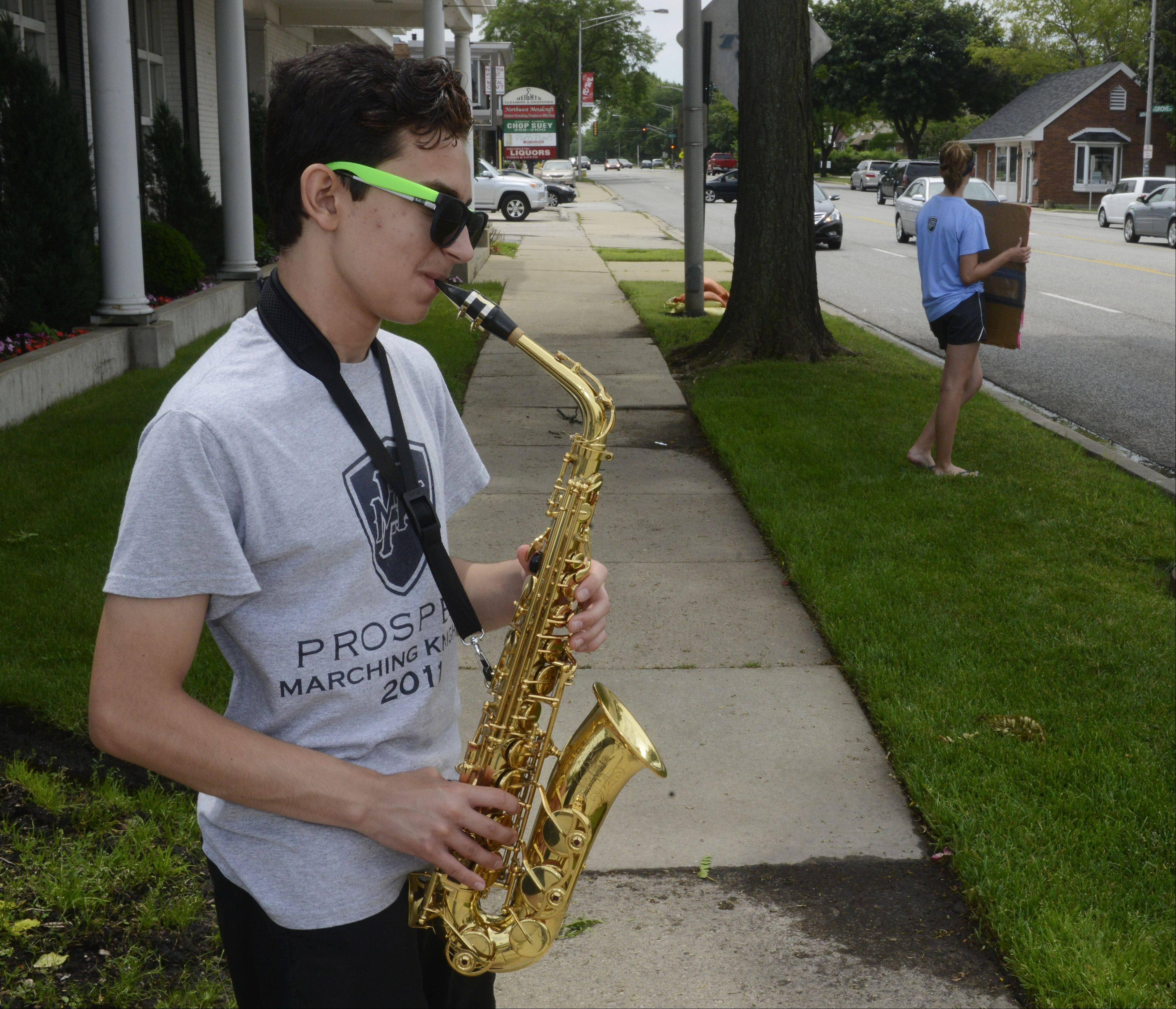 Max Arnold, a Prospect High School junior, tries to lure drivers into the car wash on Arlington Heights Road with the sweet sounds of his saxophone.