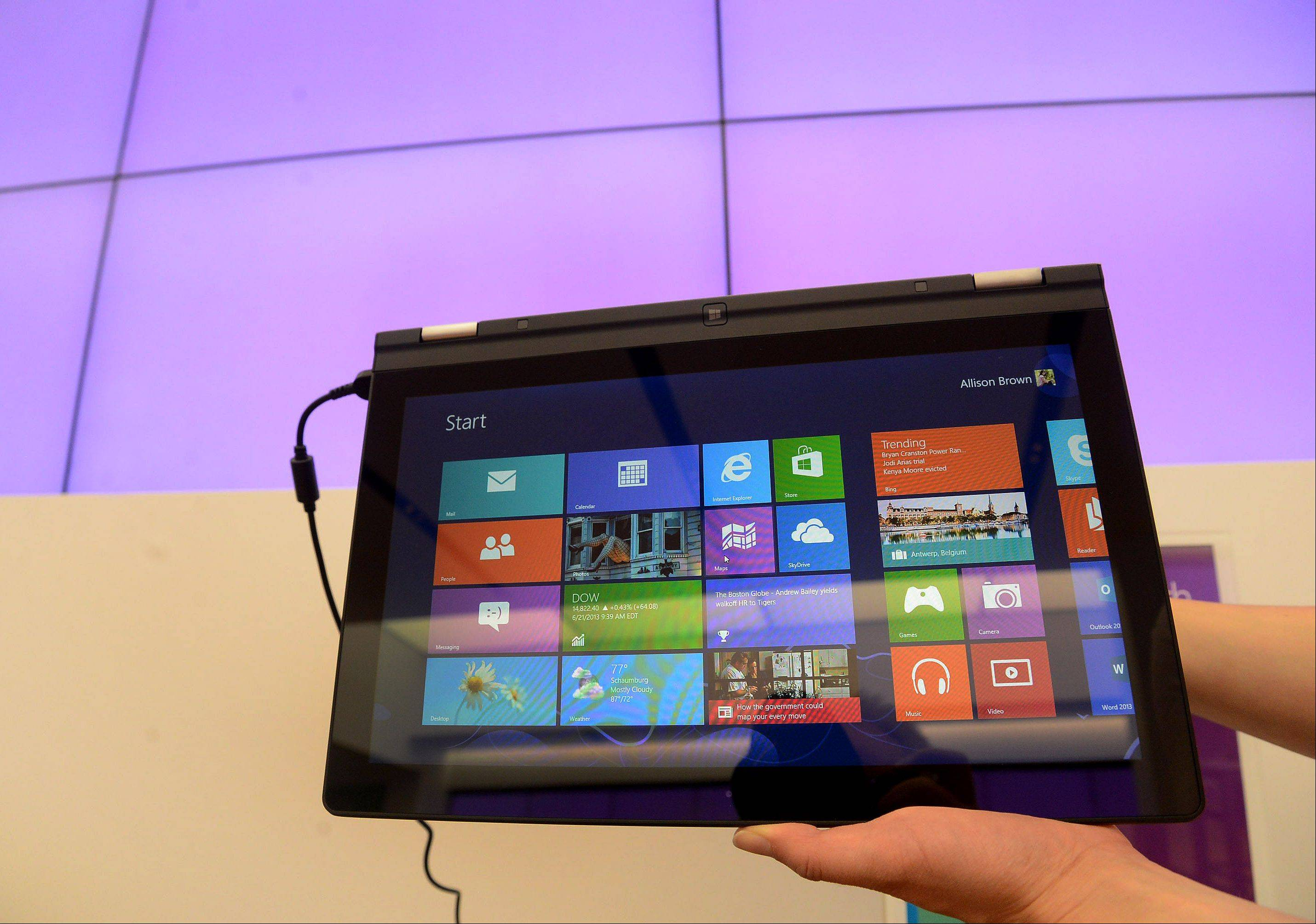 Lucretia Taylor, public relations assistant, displays the Lenovo IdeaPad Yoga i5 with Windows 8 operating system.