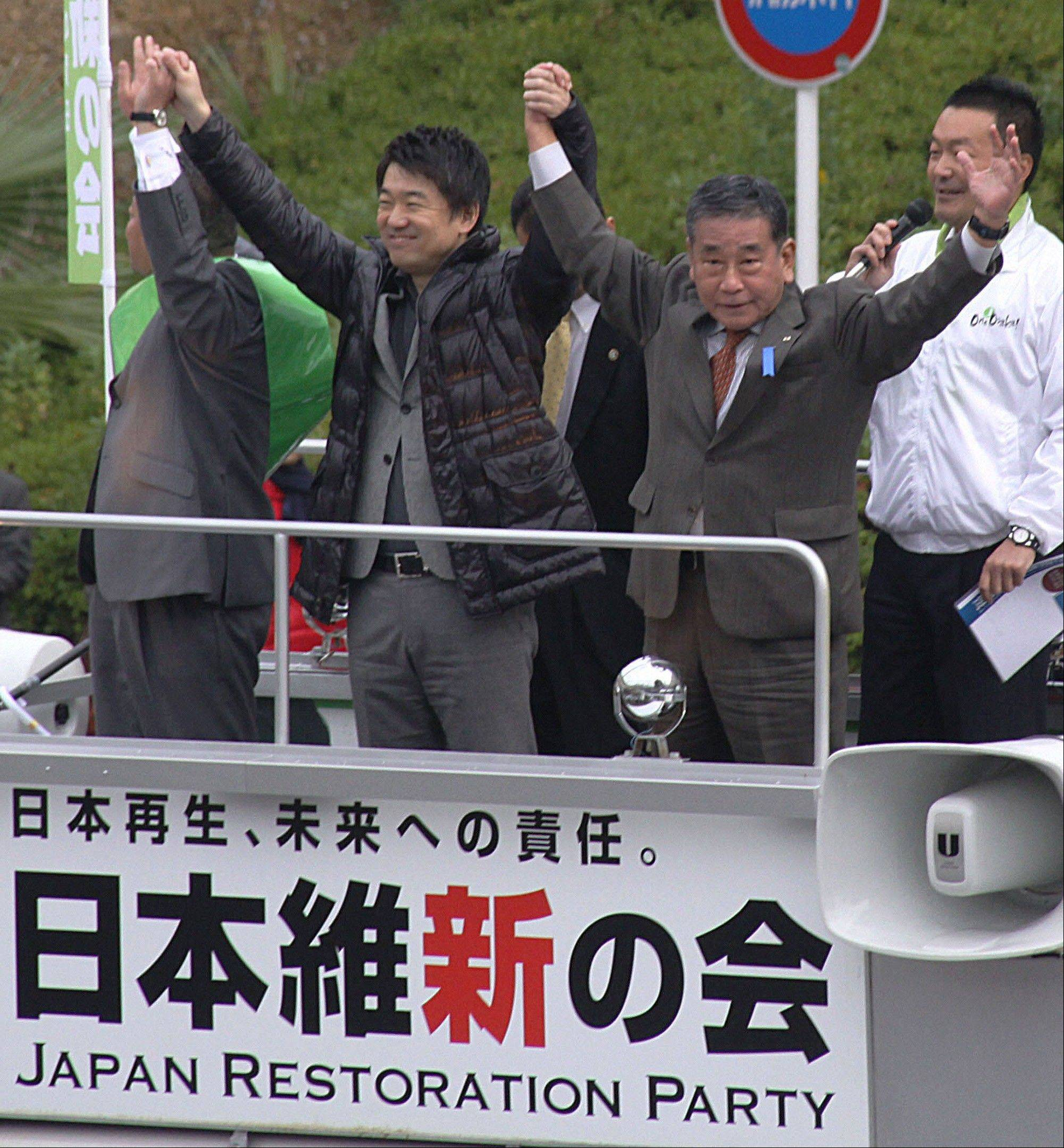 Osaka Mayor and co-leader of the Japan Restoration Party Toru Hashimoto, foreground center, along with Shingo Nishimura, foreground right, a former member of the House of Representatives, wave to supporters during their party's election campaign in Sakai, Osaka prefecture, western Japan. Hashimoto apologized after saying, and later tweeting, that sex slavery by Japan's Imperial Army before and during World War II was a 'necessary' wartime evil and suggesting that the U.S. military patronize adult entertainment to help reduce sex crimes committed by American troops.