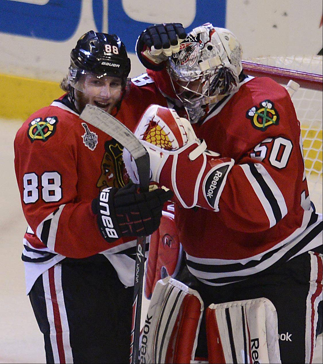 Chicago Blackhawks right wing Patrick Kane and goalie Corey Crawford congratulate each other after the 3-1 win over the Boston Bruins Saturday in Game 5 of the Stanley Cup Finals at the United Center in Chicago.