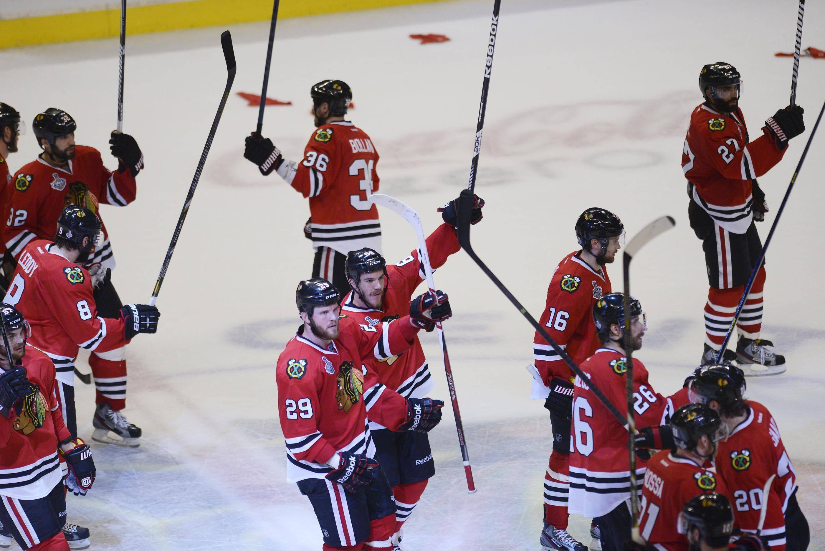 The Chicago Blackhawks raise their sticks after defeating the Boston Bruins Saturday in Game 5 of the Stanley Cup Finals at the United Center in Chicago.