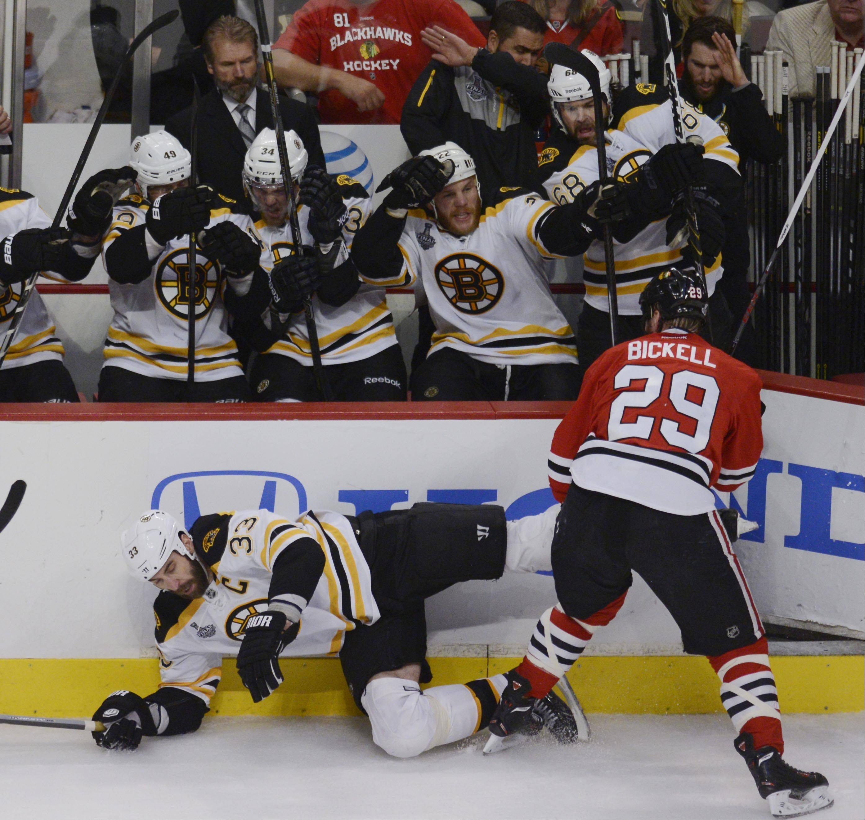 Chicago Blackhawks left wing Bryan Bickell checks Boston Bruins defenseman Zdeno Chara into the boards in front of the Boston bench in the first period Saturday in Game 5 of the Stanley Cup Finals at the United Center in Chicago.