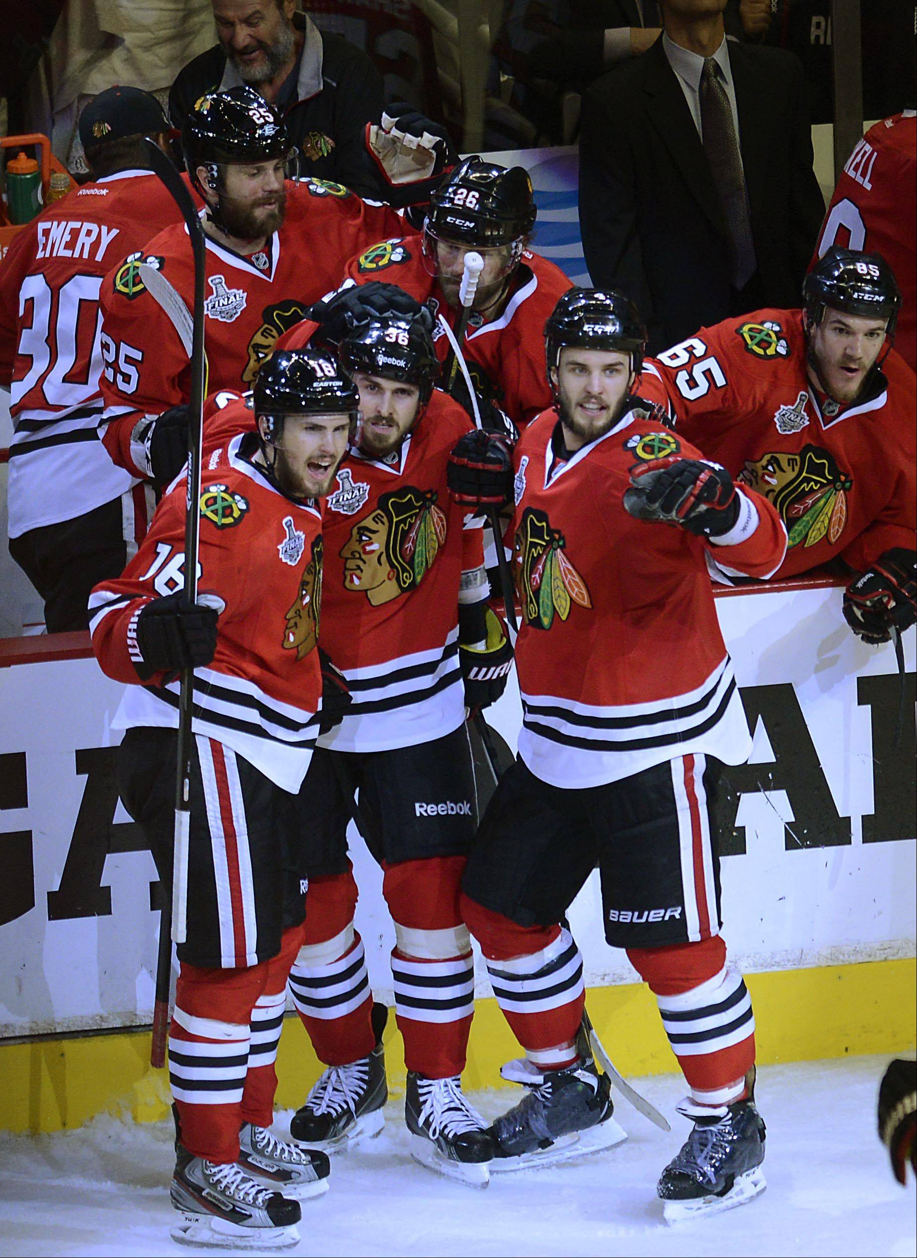 Chicago Blackhawks center Dave Bolland is surrounded by teammates after his empty-net goal late in the third period that sealed the win over the Boston Bruins Saturday in Game 5 of the Stanley Cup Finals at the United Center in Chicago.