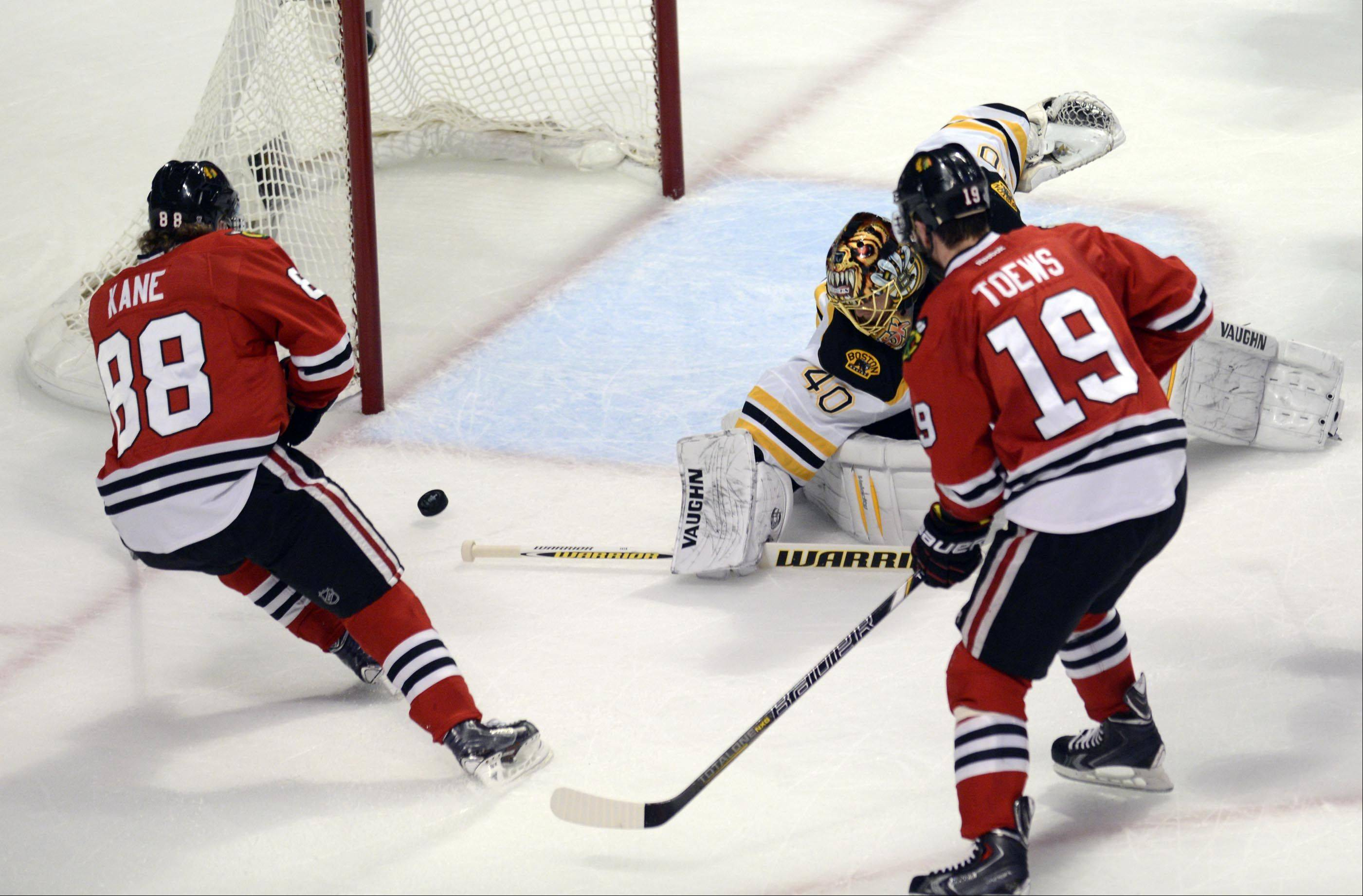 Chicago Blackhawks center Jonathan Toews passes the puck to teammate Patrick Kane who scores in the first period against Boston Bruins goalie Tuukka Rask Saturday in Game 5 of the Stanley Cup Finals at the United Center in Chicago.