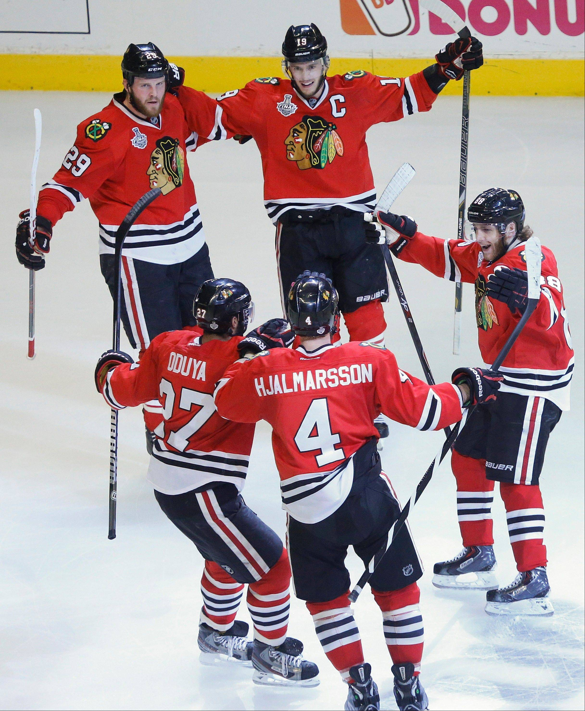 The Chicago Blackhawks celebrate a first period goal against the Boston Bruins during Game 5 of the NHL hockey Stanley Cup Finals, Saturday, June 22, 2013, in Chicago.