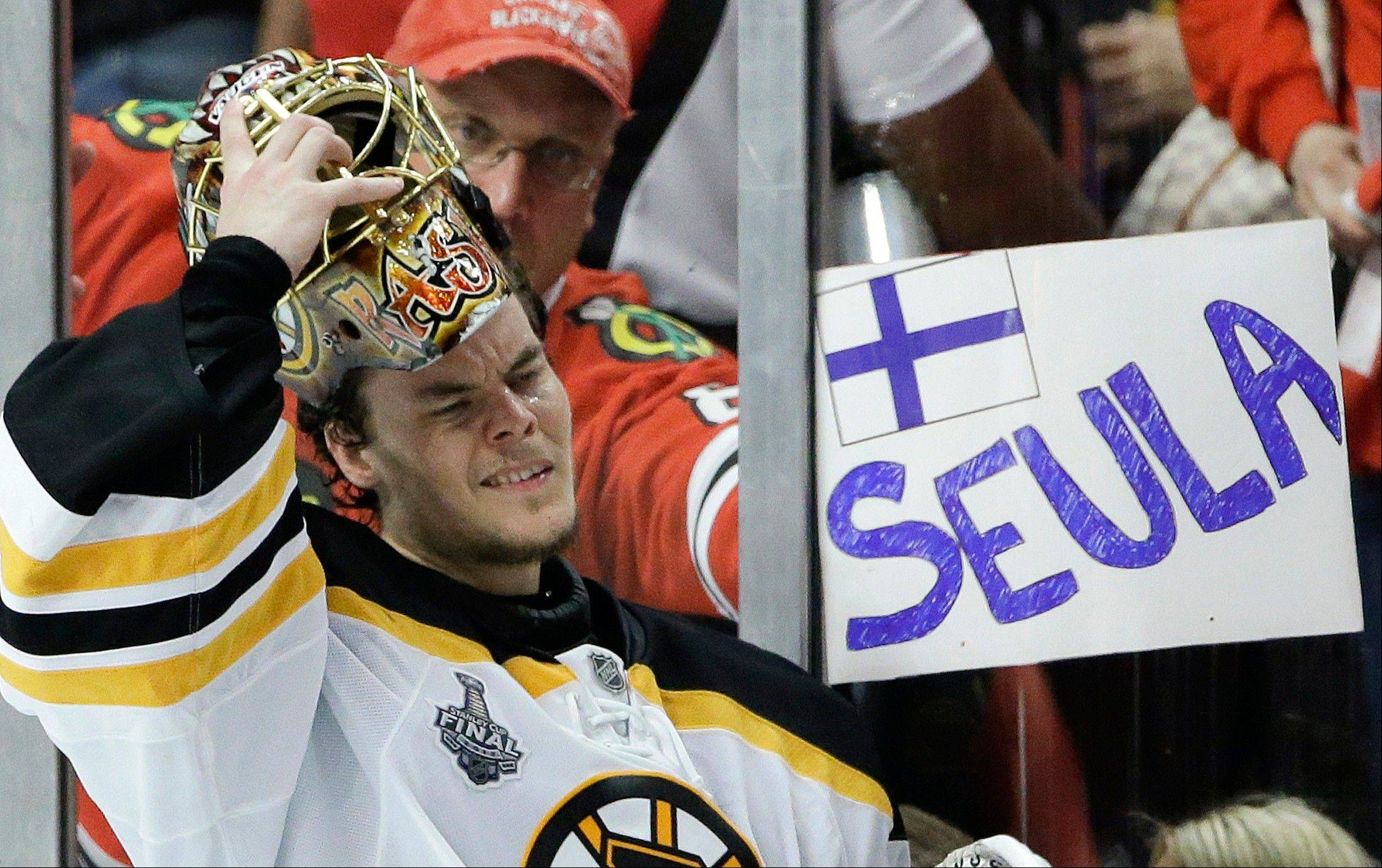 Boston Bruins goalie Tuukka Rask (40) puts his mask back on after a break in the third period against the Chicago Blackhawks as a fan holds up a sign in Finnish calling Rask a hockey sieve in English, during Game 5 of the NHL hockey Stanley Cup Finals, Saturday, June 22, 2013, in Chicago.