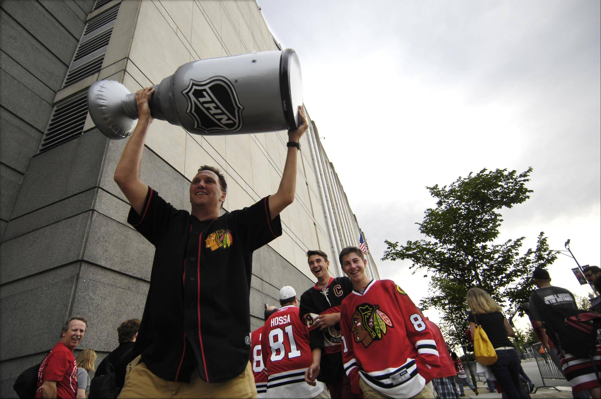 Yaro Dachniwsky carries a replica Stanley Cup with sons Alex and Adrian Saturday before Game 5 of the Stanley Cup Finals at the United Center in Chicago. They are from Lake Forest.