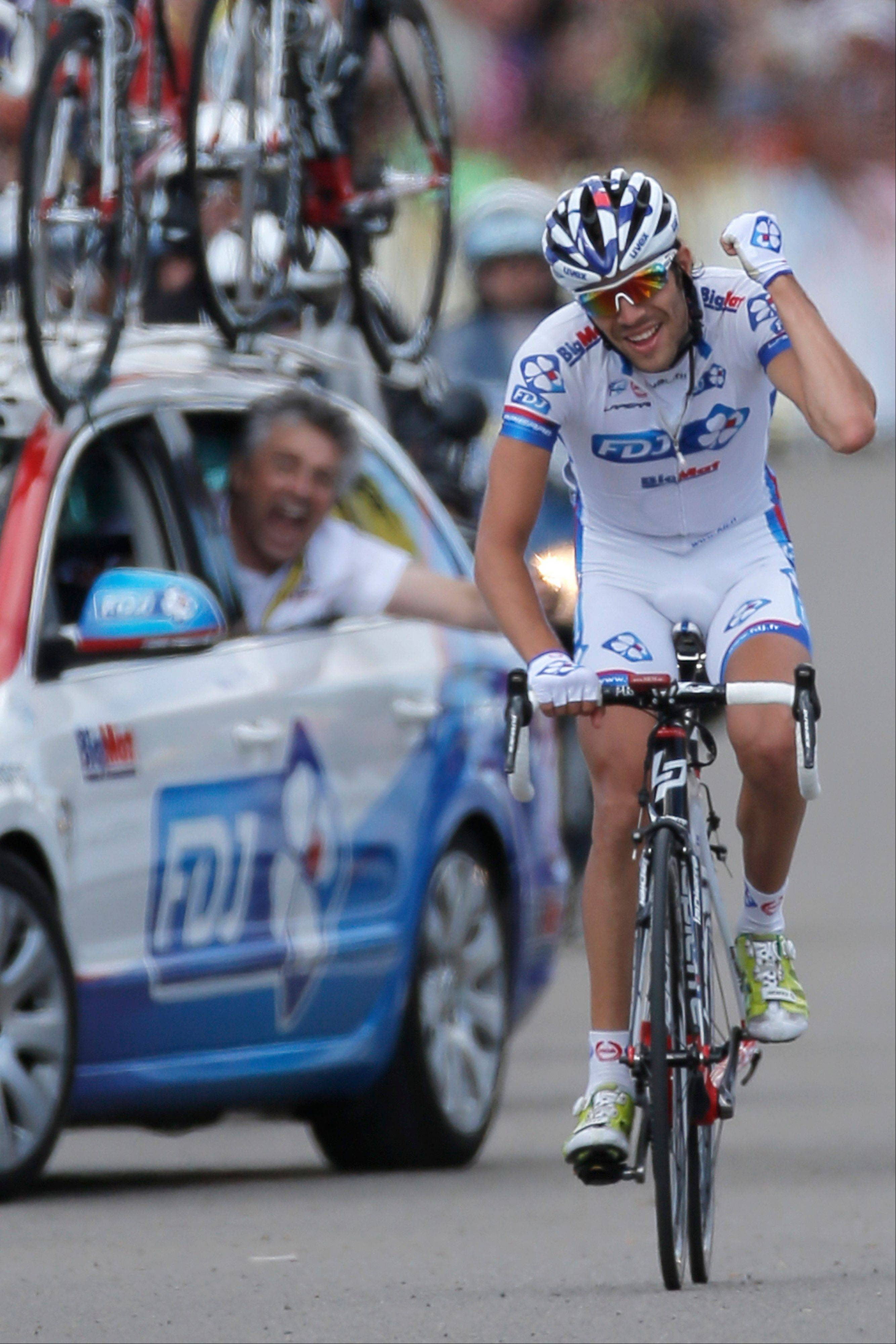 Team director Marc Madiot, left, celebrates in his car as Thibaut Pinot crosses the finish line to win the eighth stage of the Tour de France in 2012