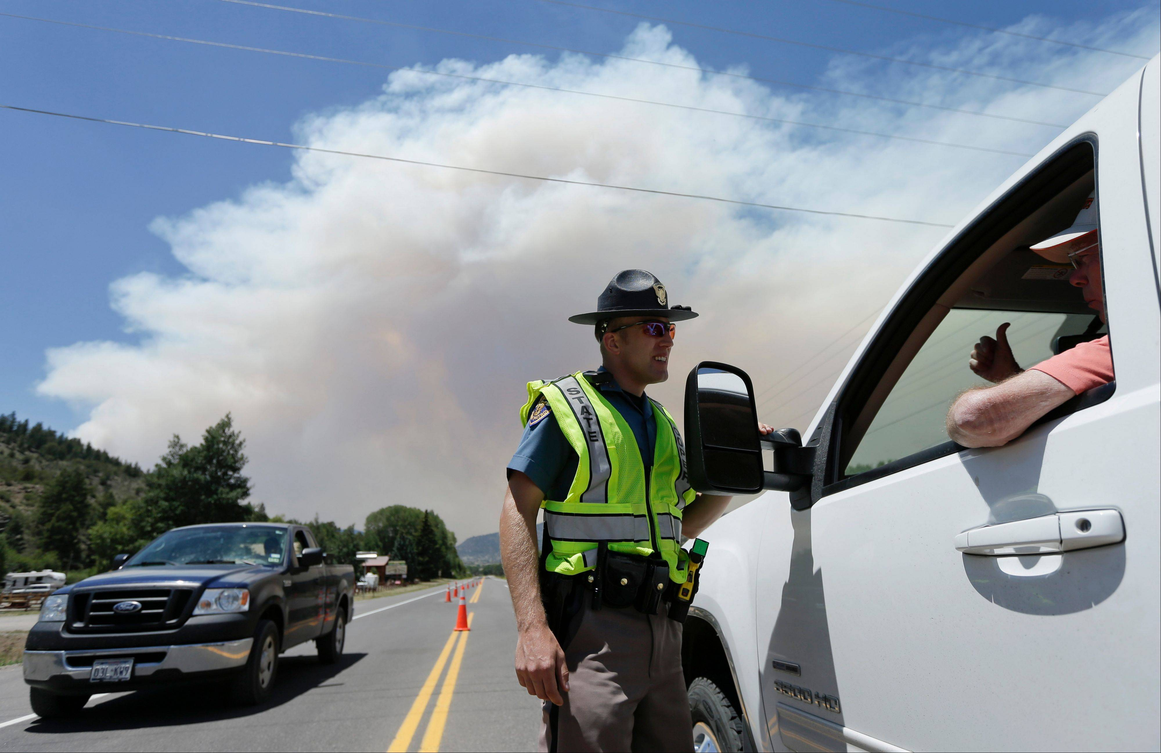 Colorado State Patrol officer Jessie Bartunek talks to a motorist as he stands at a checkpoint near South Fork, Colo., Sunday. A large wildfire near a popular summer retreat in southern Colorado continues to be driven by winds and fueled by dead trees in a drought-stricken area, authorities said Sunday.