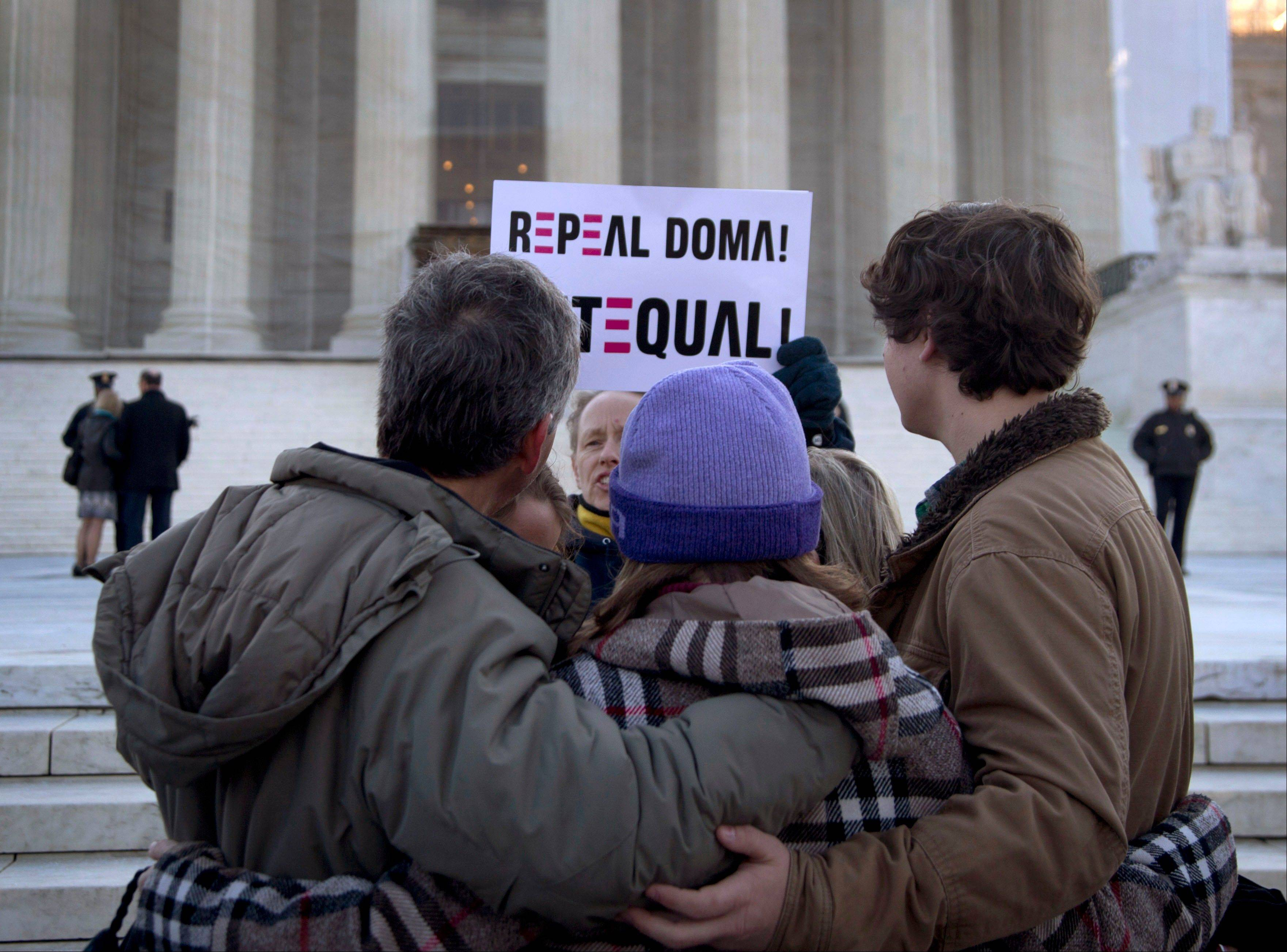In this March 27, 2013, file photo a woman holds up a sign that reads �REPEAL DOMA,� the Defense of Marriage Act in front of a group from Alabama, clasped in prayer in front of the Supreme Court in Washington, as the court hears arguments on gay marriage. Sometime this early July, the Court will announce the outcomes in cases on Californian�s ban on same-sex marriage, Proposition 8, and the federal Defense of Marriage Act, the federal law that defines marriage as the union of a man and a woman.