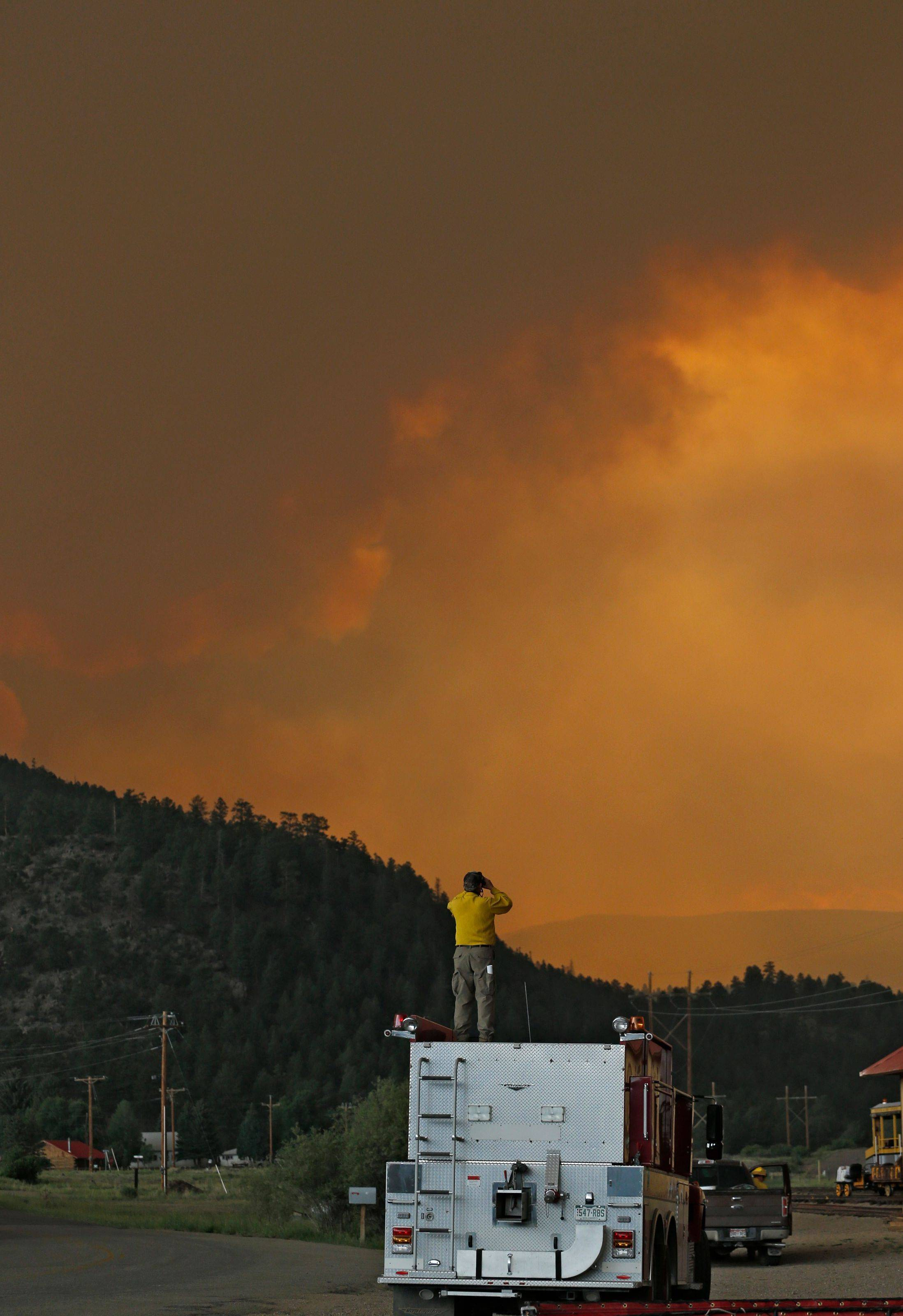 A firefighter stands on top of a firetruck Friday evening in South Fork, Colo., as he monitors a wildfire that burns west of town. The town was evacuated and U.S. 160 that passes through it was closed.