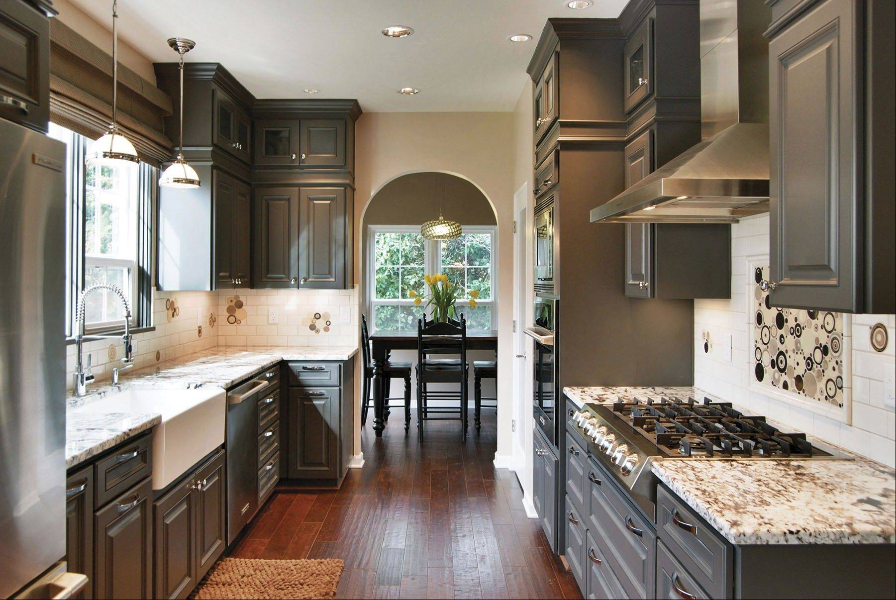Dark, warm gray cabinets have a sleek finish and ground this traditional kitchen design. A black and white backsplash gives it extra pop.