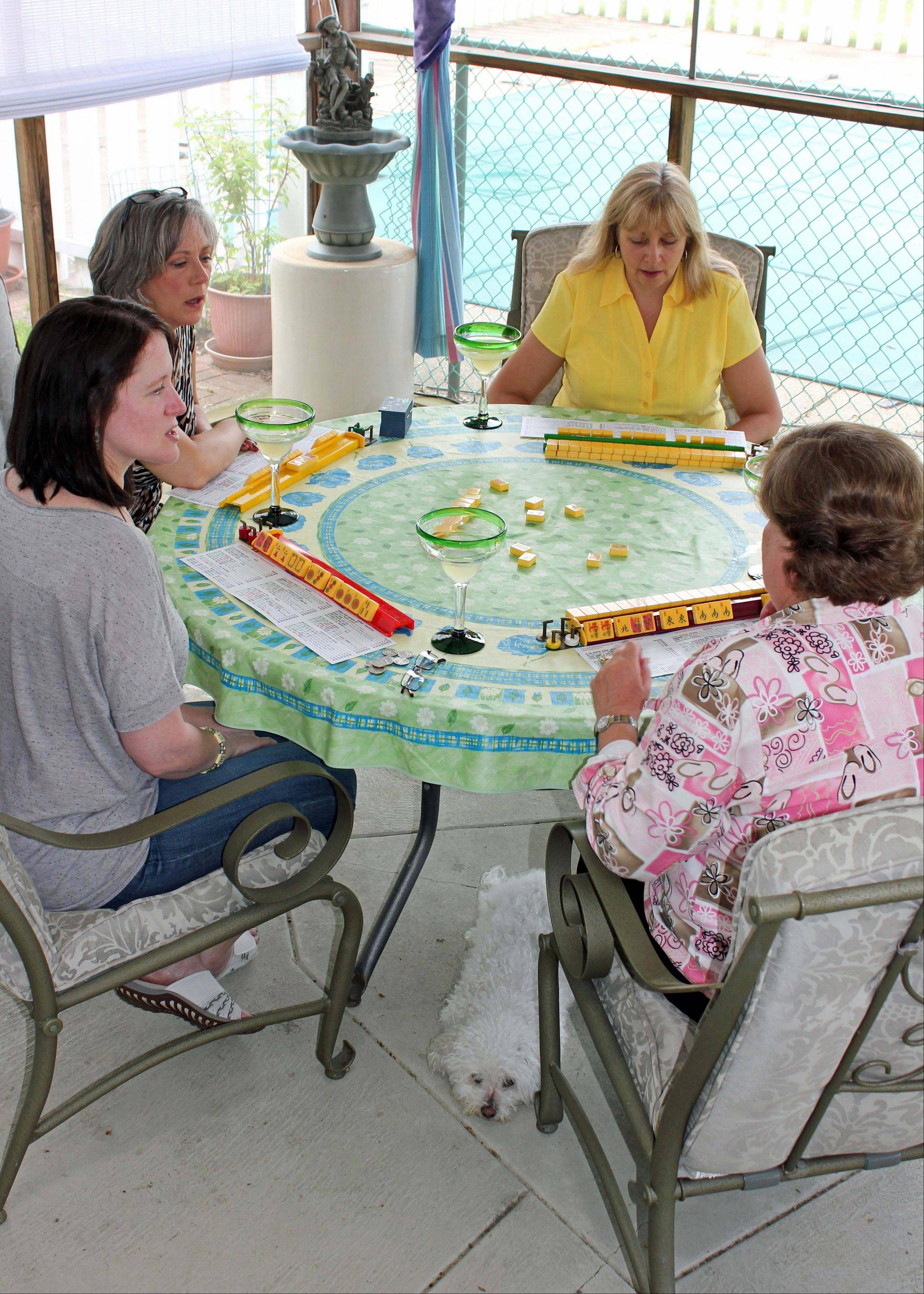Debbie Schwartz, left, Marcy Imperi, Benita Munger and Judy Palladino play mahjong during a game night gathering in Mayfield Village, Ohio.