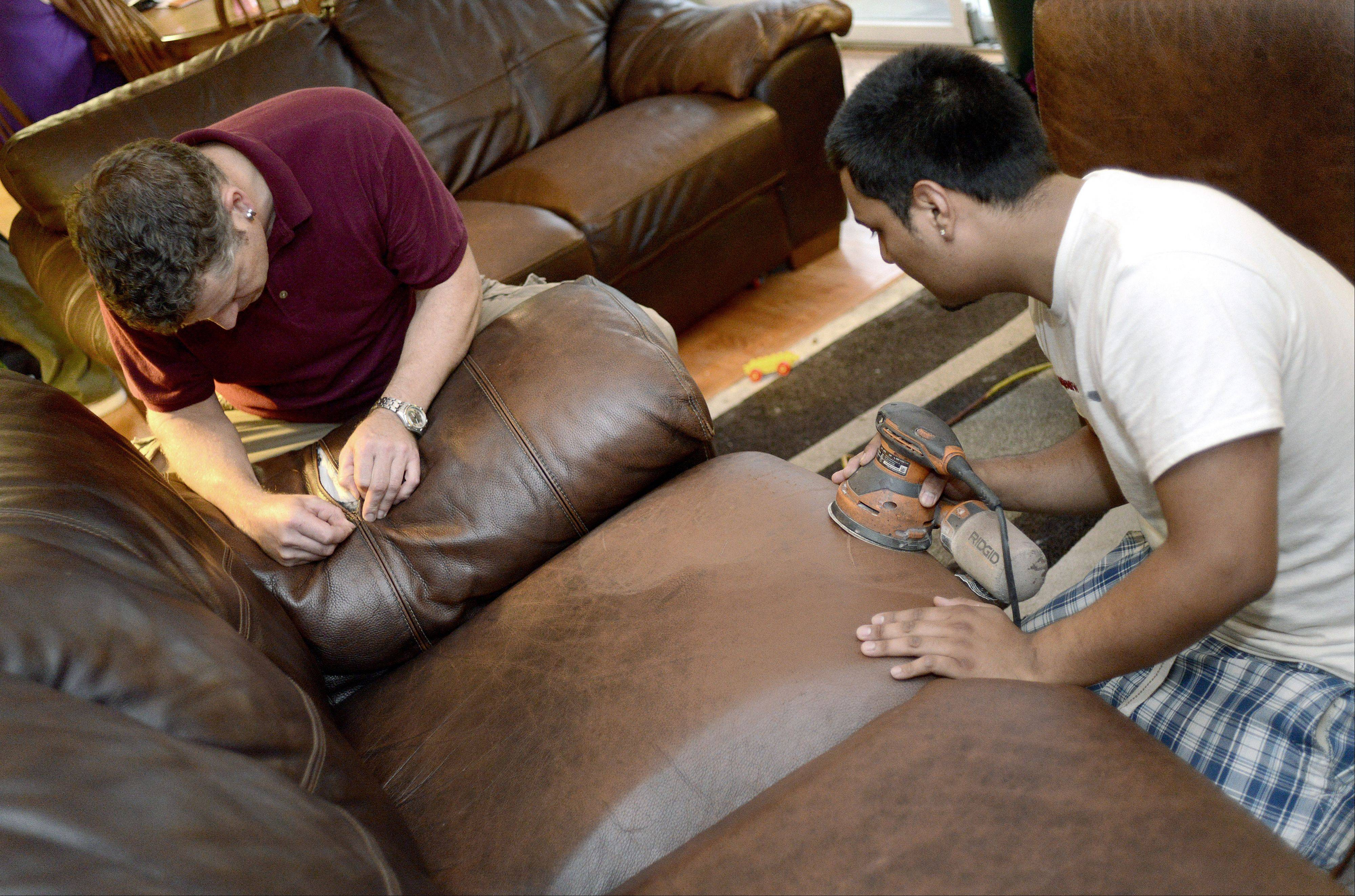 Fibrenew franchise owner Ivar Vankemenade restitches a busted seam of an armrest while Angel Gavina resurfaces the cushions on the leather couch, prepping it for restoration. Vankemenade visits clients in their homes, like this one in Elgin, and does furniture restoration work on site.