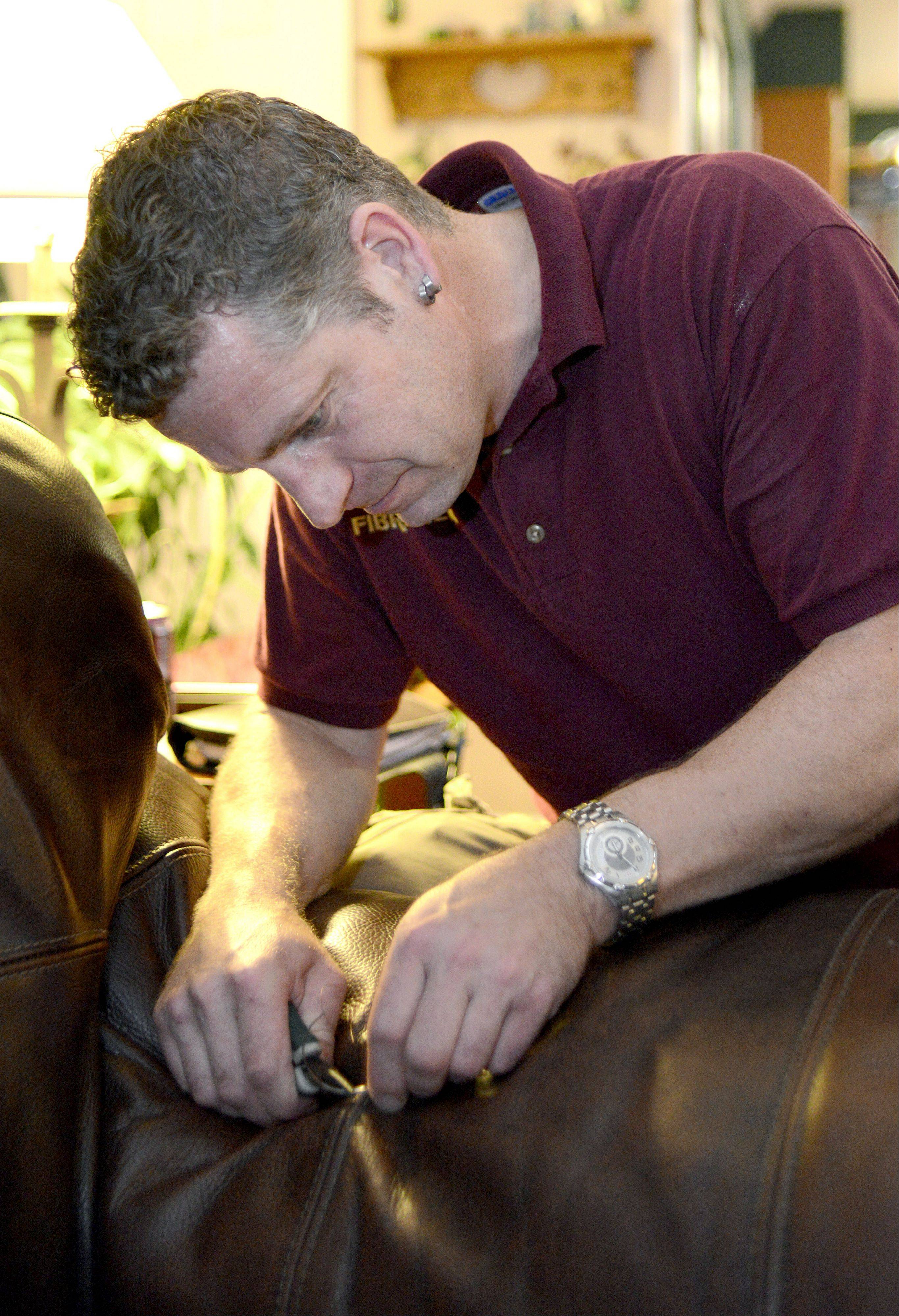 Ivar Vankemenade of Fibrenew Chicago NW restitches a busted seam on a leather couch at a client's home in Elgin. The company can fix cracks, stains, scratches, holes, rips and fades in leather, plastic, vinyl, fabric and upholstery.