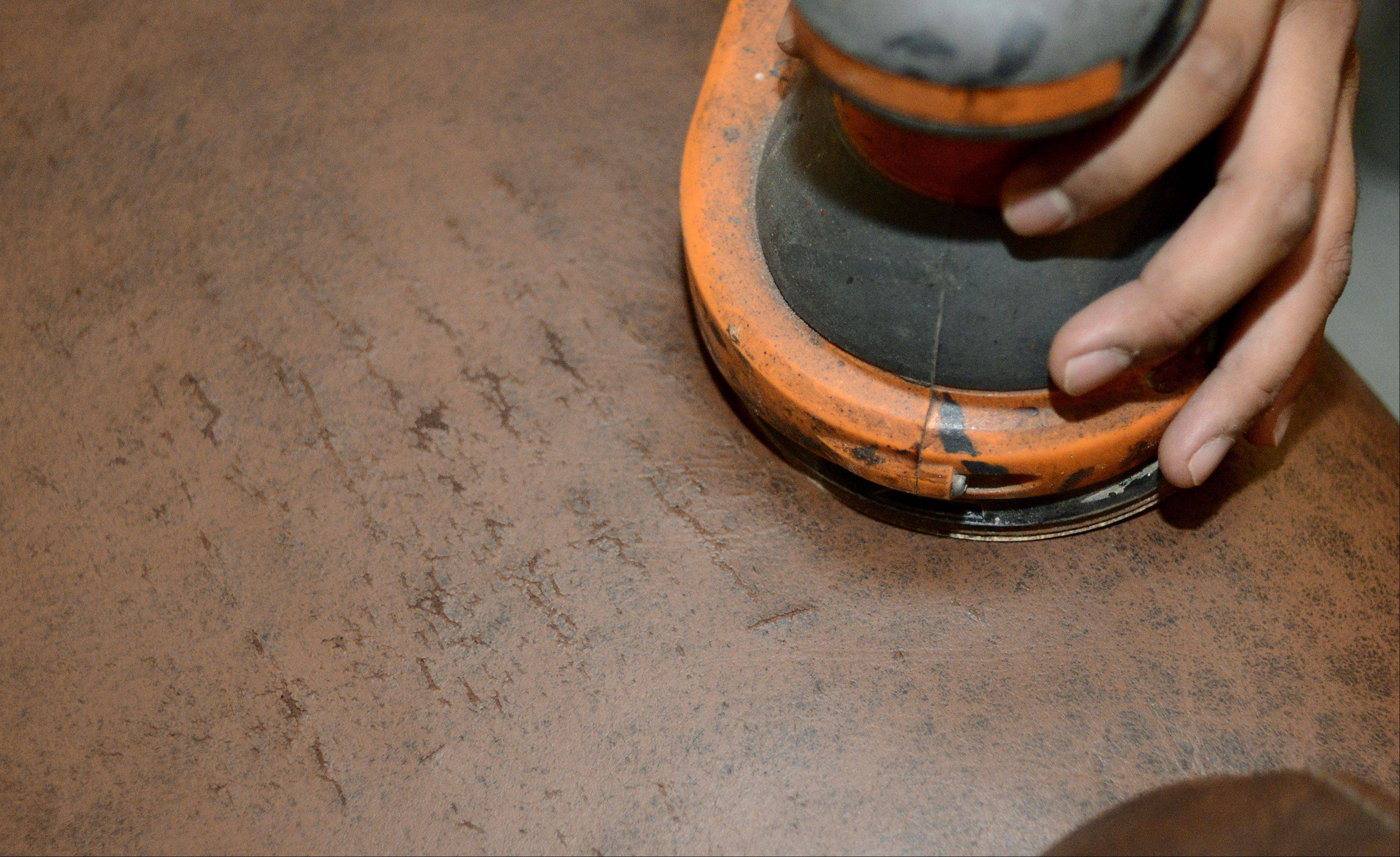 One of the steps of furniture restoration includes resurfacing with a sanding device.