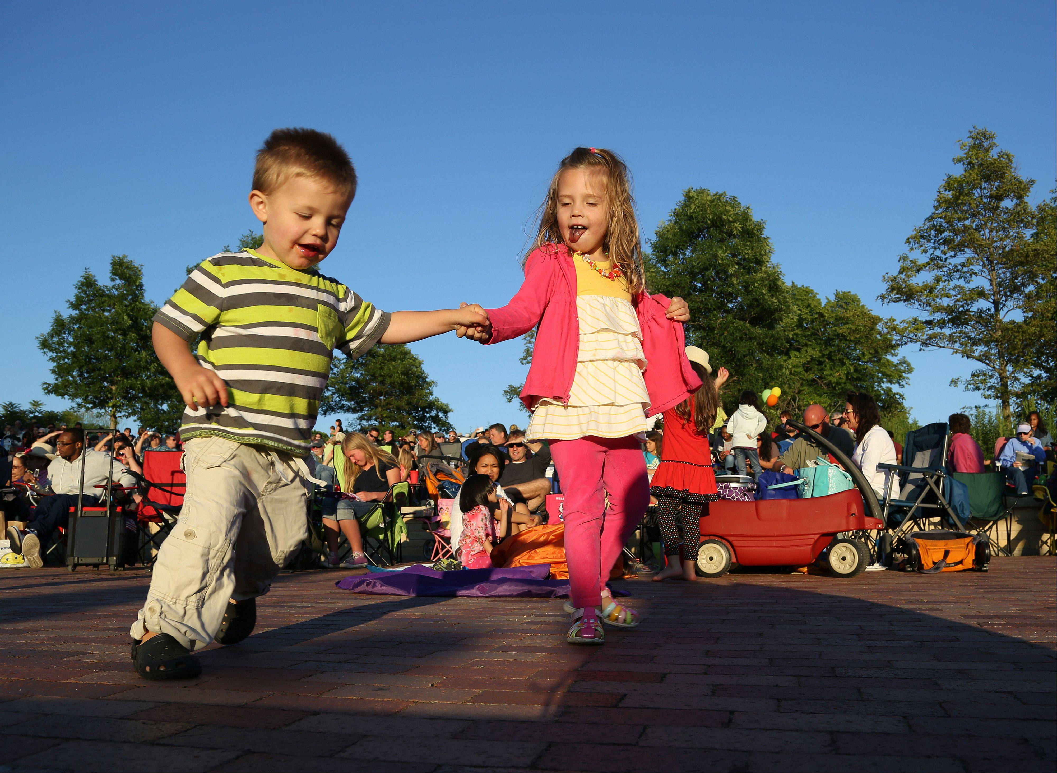 Charlie Evans, 2, and his sister Ella, 3, of Green Oaks dance to the sounds of Chicago R&B Kings during Events in the Plaza outdoor summer concert series Tuesday night at Independence Grove Forest Preserve in Libertyville.