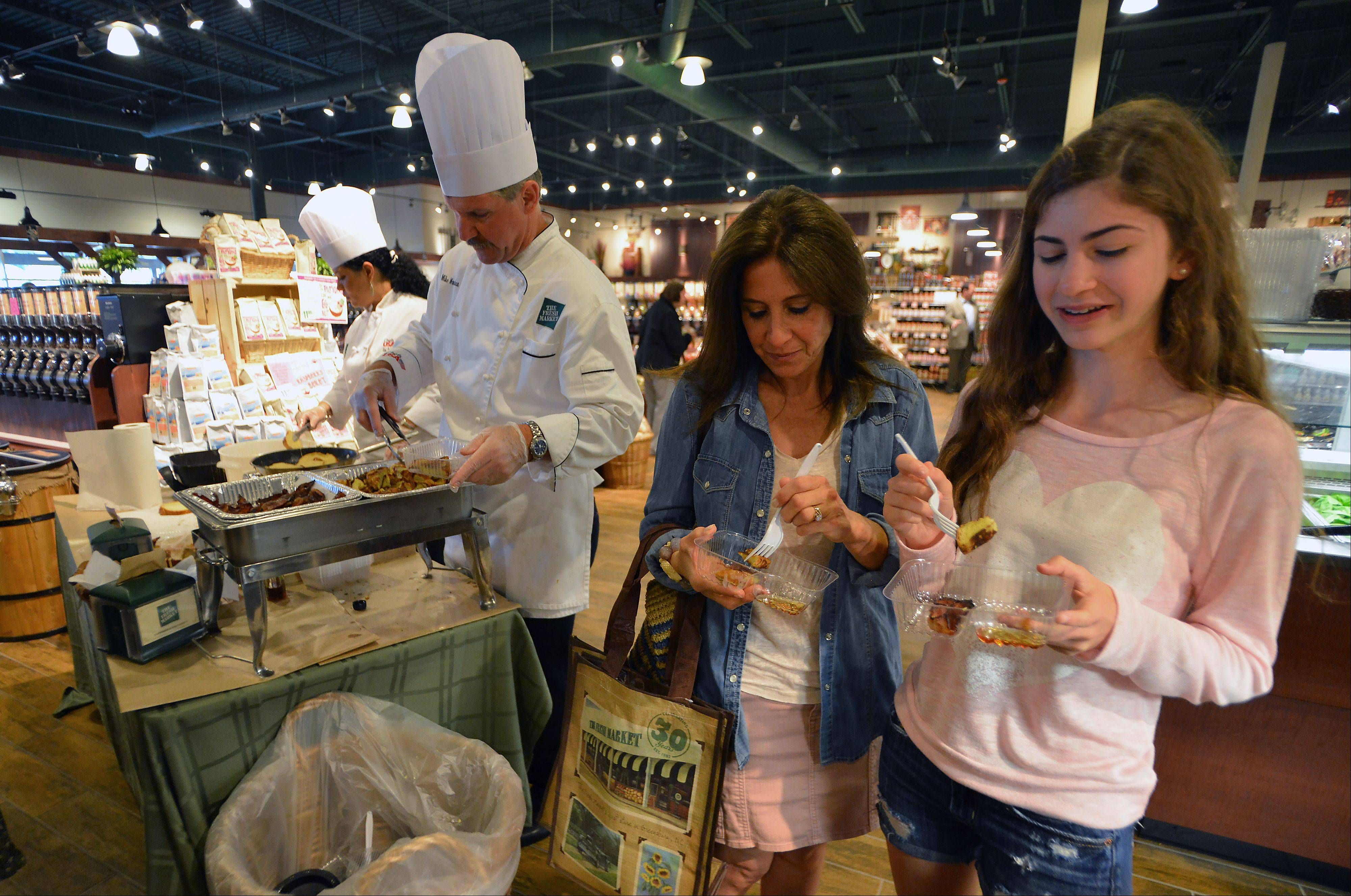 Shoppers Lori Abrams and her daughter Talia, 16, of Buffalo Grove, prepare to taste food samples from Chef Mike Monahan of Alanta, Georgia and Chef Desiree Price, of Spring Grove, at the grand opening of The Fresh Market in Lincolnshire on Wednesday.