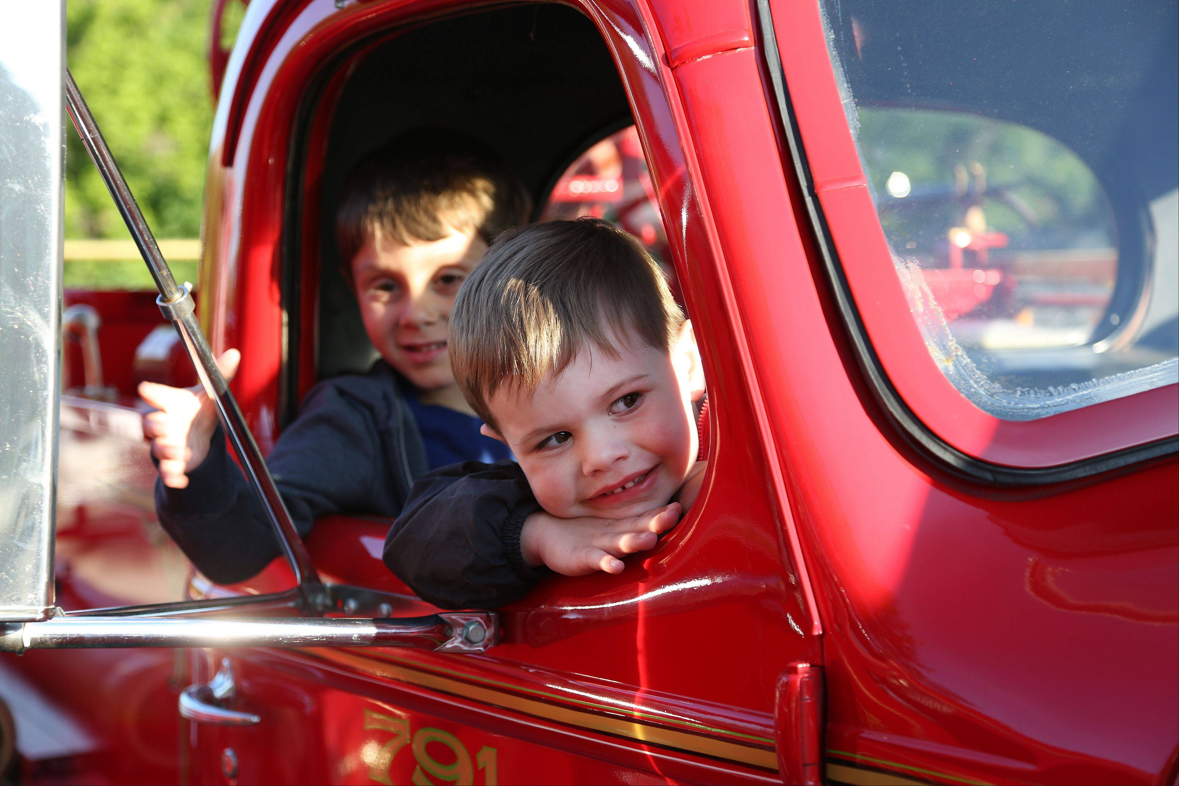 4-year-old Elliot Merryman of Libertyville, right, and 5-year-old Harrison Kaufman of Gurnee hang out the passenger window of this vintage Vernon Township fire truck at the Car Fun on 21 event in downtown Libertyville Wednesday.