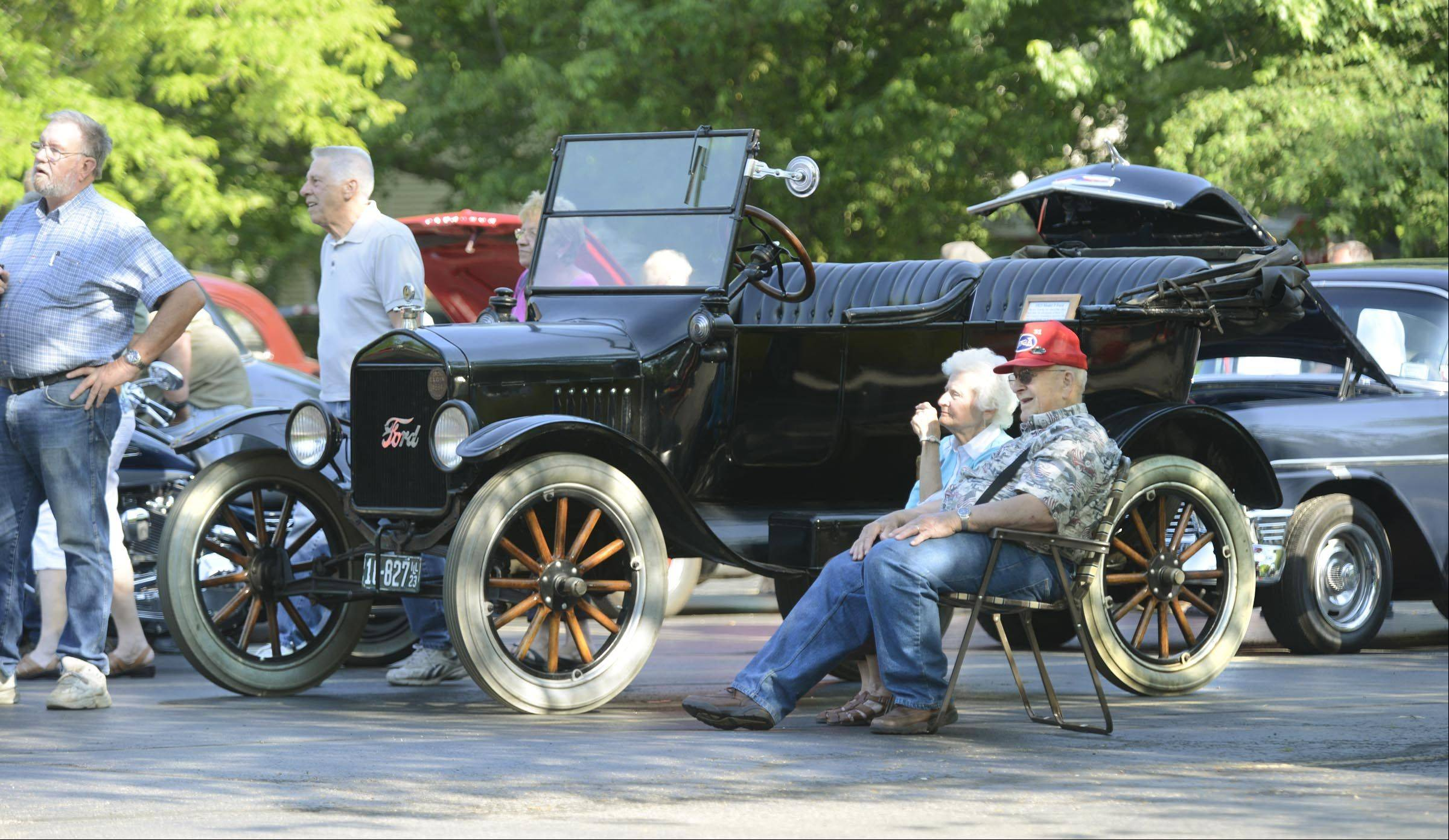 Whitey and Arlene Reiser, of Hampshire, sit in their lawn chairs in a shady part of the parking lot near a 1923 Ford Model T Roadster Wednesday evening at the third annual Elgin American Legion Post 57 car show. The Reiser's own a 1931 Ford Model A pickup truck that was on display at the show.