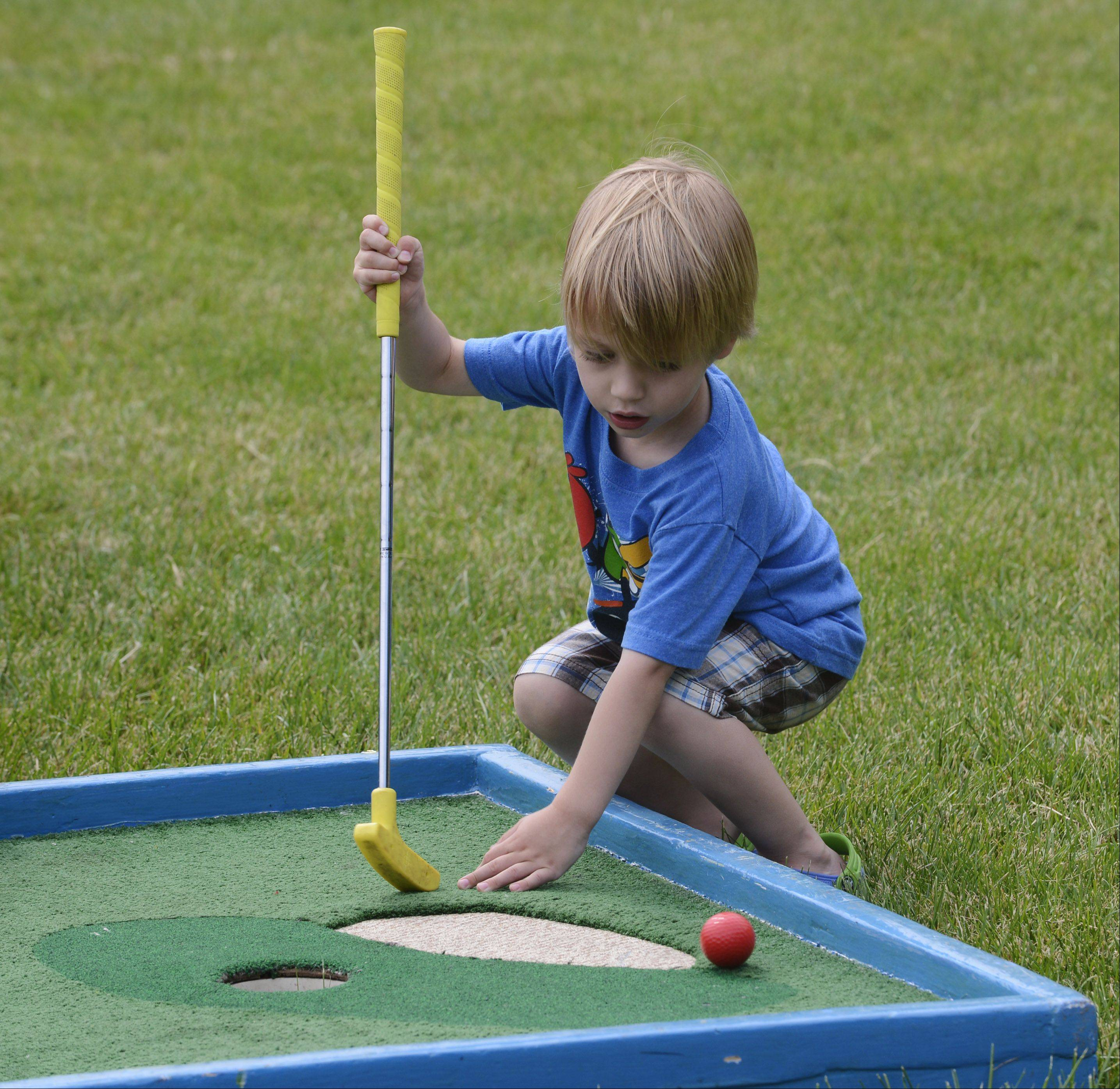 Pacific Toll, 3, of Prospect Heights gets ready to hit his ball off the edge of a sand trap while playing miniature golf at the Prospect Heights Summer Block Party at Lions Park Saturday.