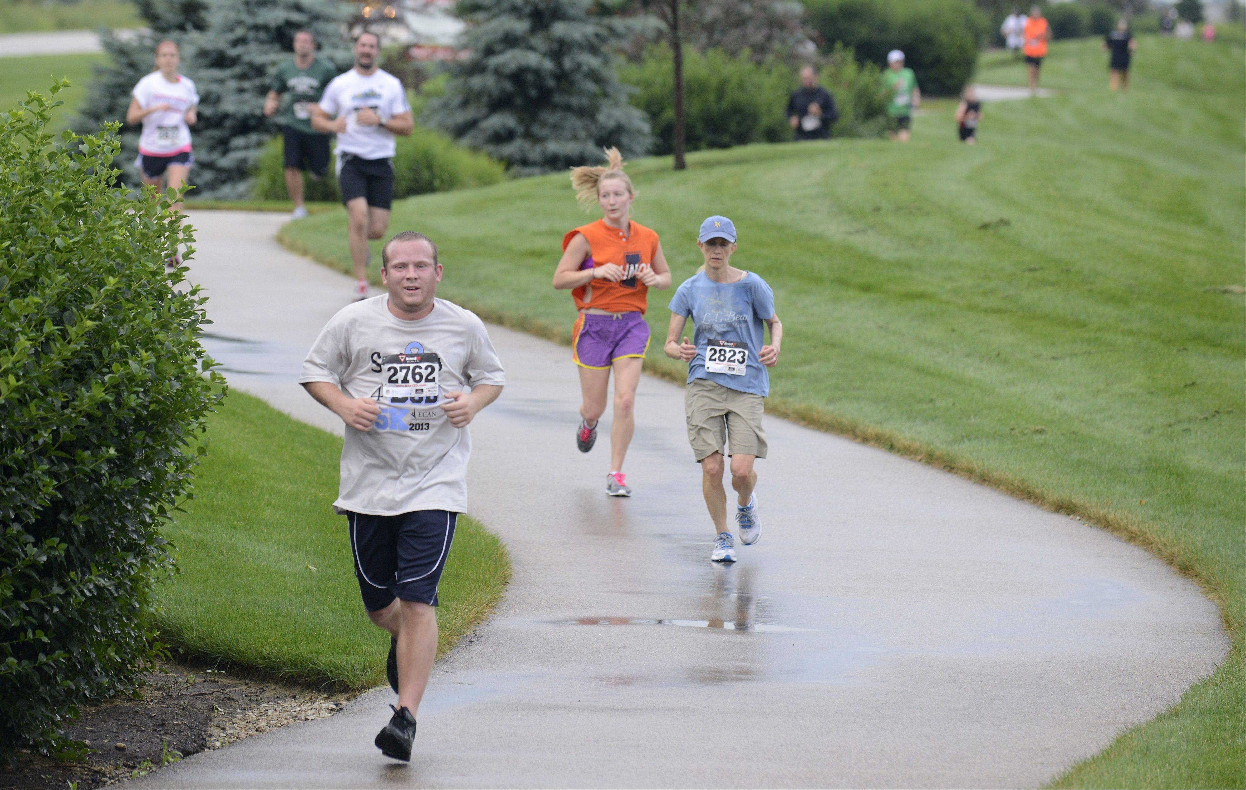Brian Fahey of Elgin and other runners wind down the path nearing the finish line for the Smiles 4 Bob 5K run in Elgin on Saturday. The run is held in honor of Elginite Bob Geier who passed away from Esophageal Cancer in May 2011 at the age of 52. Fahey has been best friends with Lucas Geier, son of Bob, since childhood and said he considered Bob to be like a father to him.