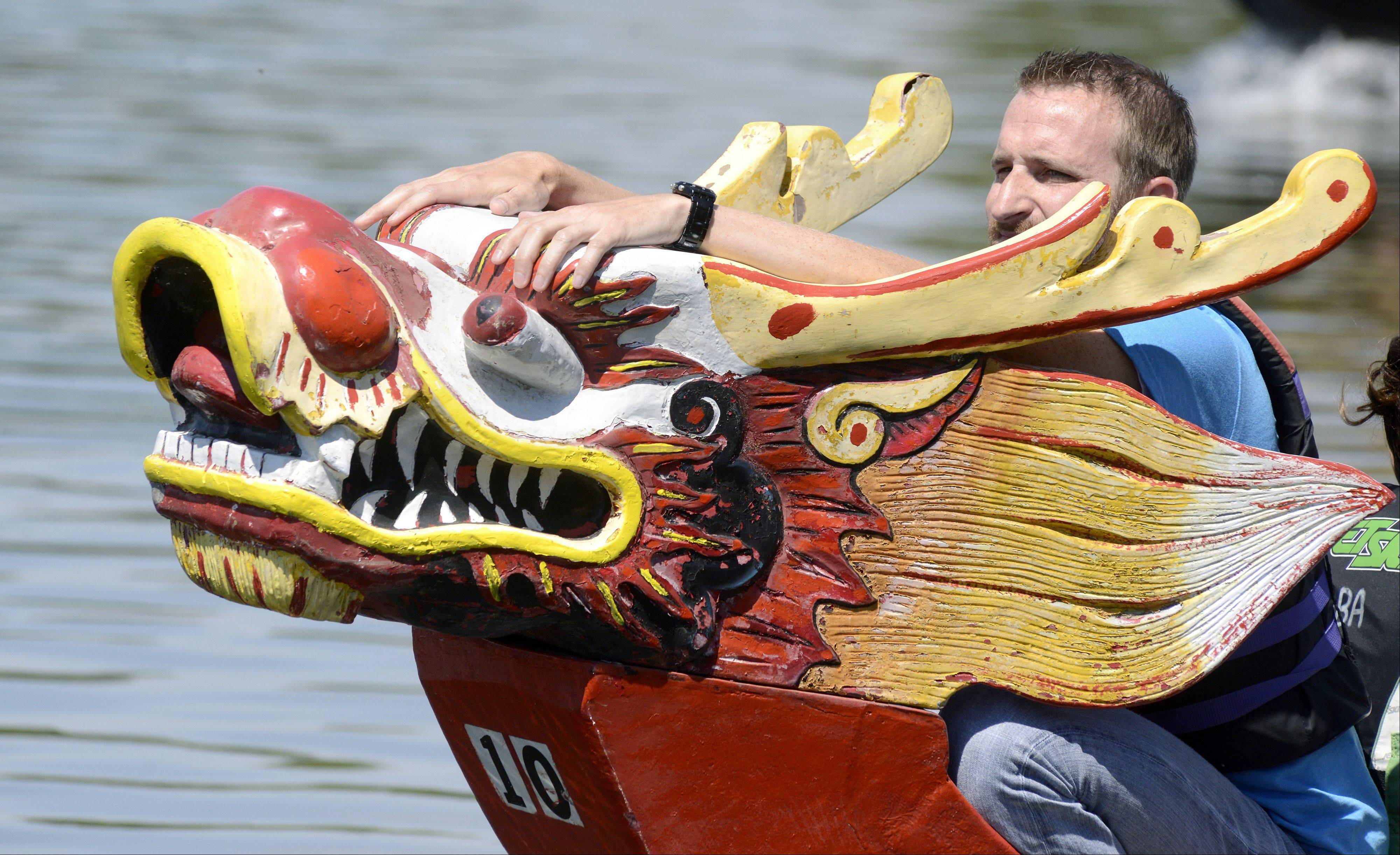 "Jonny Walker of St. Charles and team ""Jump Ship"" waits for the moment to climb atop the dragon head to grab the flag for the win during the annual dragon boat races at St. Charles' RiverFest. I've shot this event for many, many years and it's always fun to watch because the teams are excited and pumped up to start their races, that's why I chose it for the Perspective column."