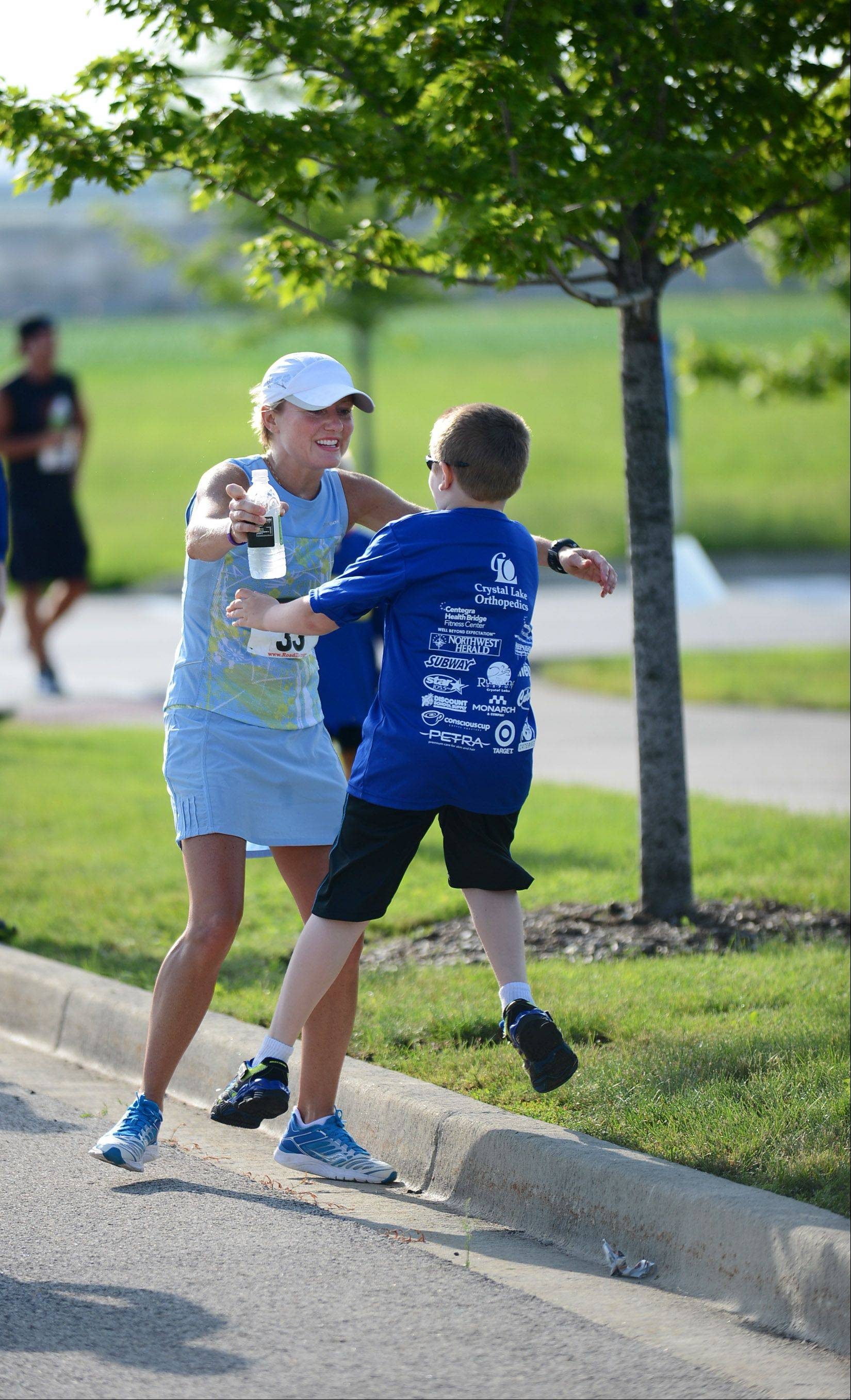 Connor Dampier, 8, jumps into the arms of his mother Angela, after she completed the 13th annual Roadrunner's 5K. The event took place Sunday at the Centegra Health Bridge Fitness Center in Huntley.