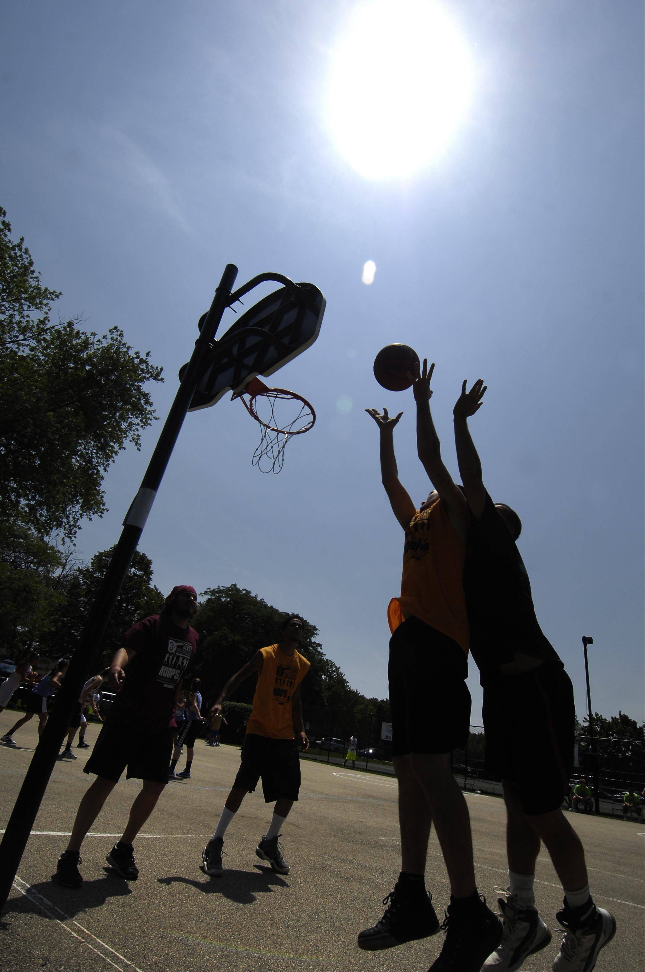 Players compete under the hot sun Sunday at the Sean Toedman Memorial 3-on-3 basketball tournament at Lions Park in East Dundee.
