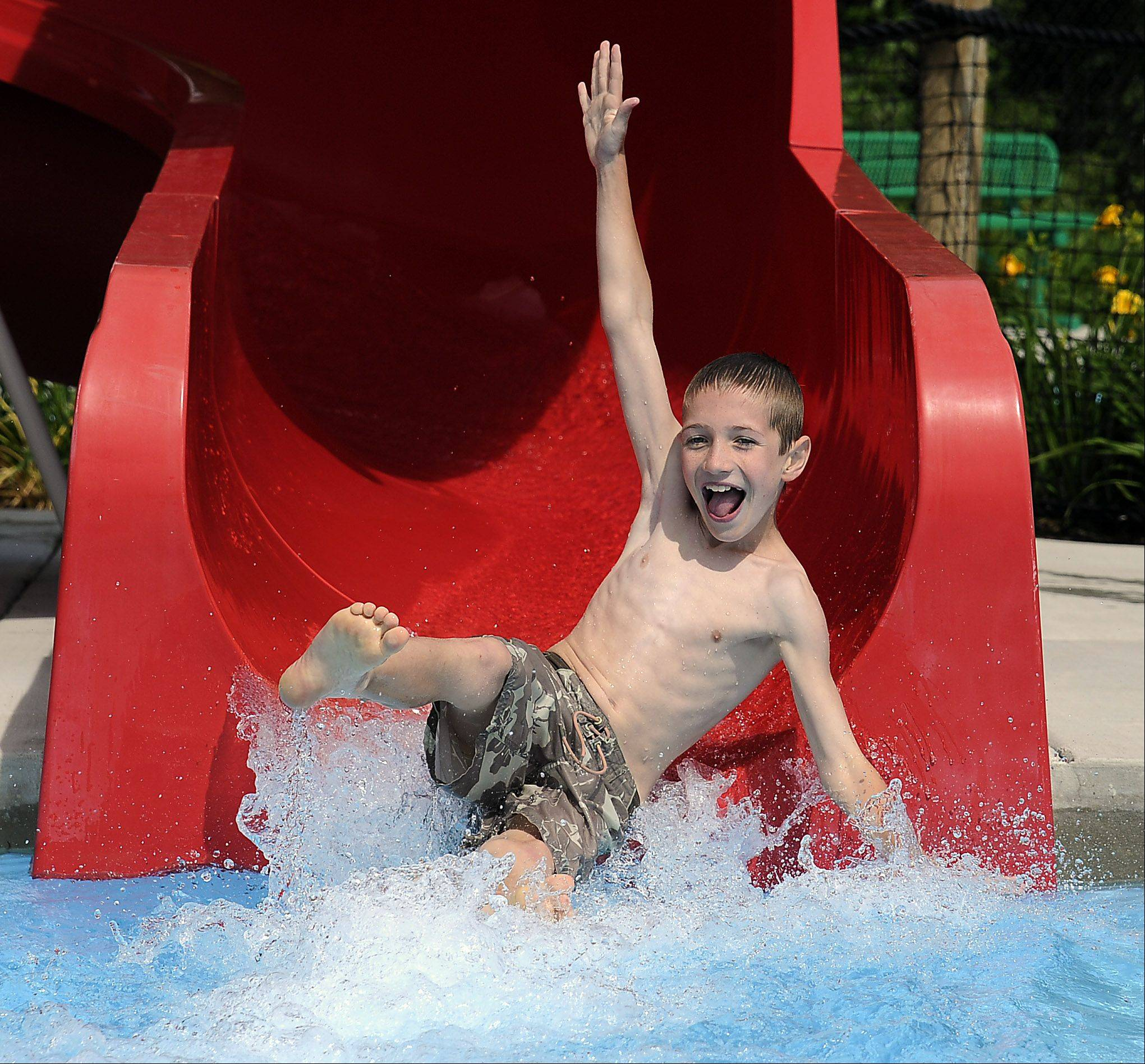 Summer fun is in full swing at Eagle pool in Palatine according to Carson Palmer, 10, of Palatine as he beats the heat splashing his way down the water slide with his buddies.