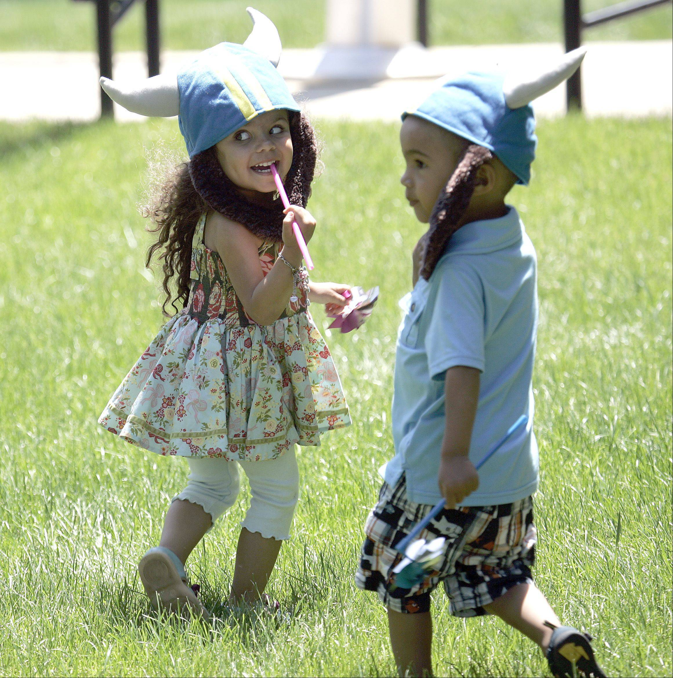 Dancing on the grass as the music kicks off, three-year-old twins, Max Naylor, right, and Charlie, left, of Geneva are complete with Viking hats and beards during a concert on the lawn at Geneva Court House Tuesday during Swedish Days Festival.