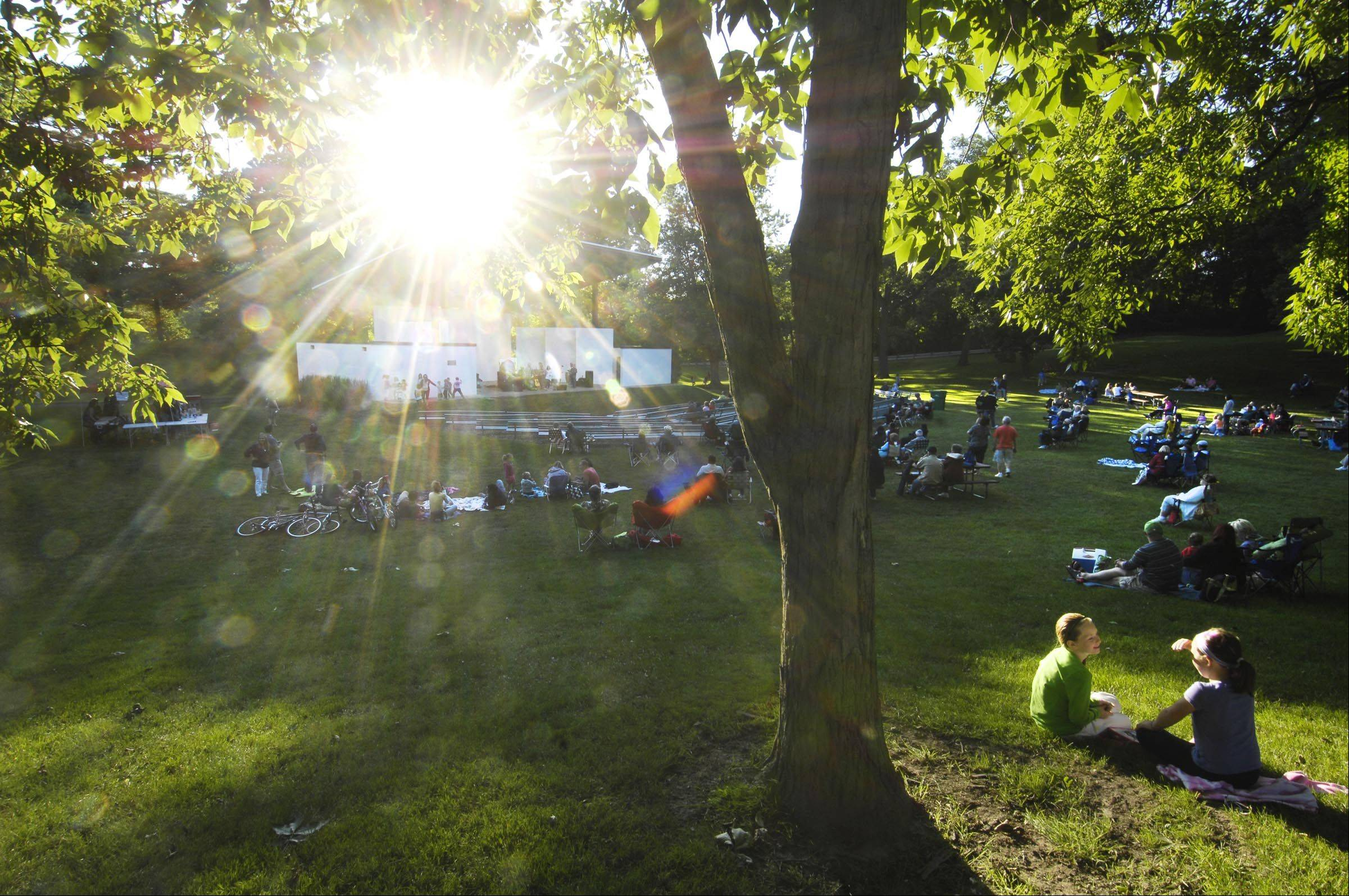 Sun beams through the summer leaves as people relax on the grass and listen to the Saturday June Band in the Wing Park bandshell in Elgin Tuesday evening. It was the opening night of the Summer Concerts in the Park series, that features music every Tuesday. Some members of the Saturday June Band are originally from Elgin.