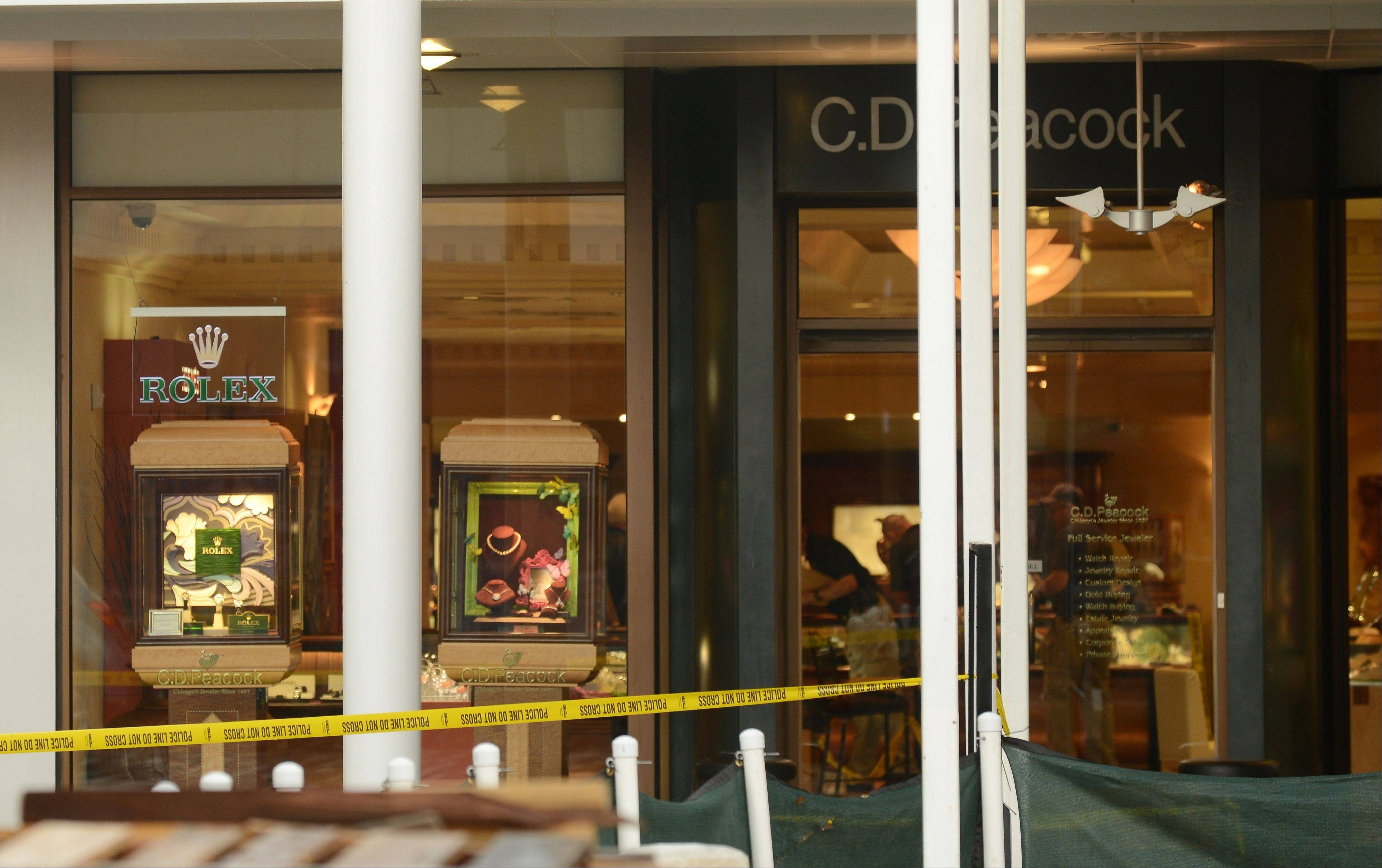 Police tape surrounds the entrance to the C.D. Peacock jewelry store at Oakbrook Center mall after gunfire erupted Sunday afternoon during an attempted robbery. Police said a robbery suspects was shot in the abdomen by a security guard while two other suspects escaped.