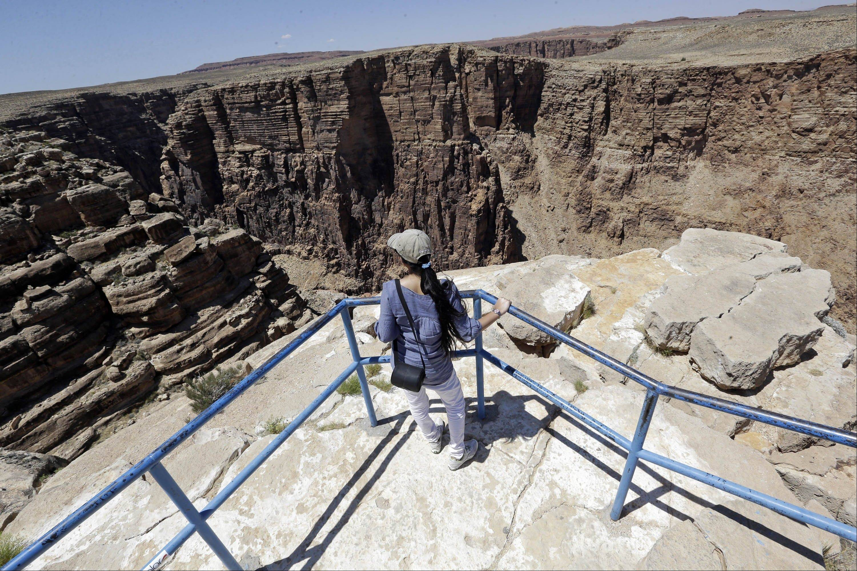 A tourist looks over the Little Colorado River Gorge Saturday on the Navajo reservation near Cameron, Ariz. The site is outside the boundaries of Grand Canyon National Park, near where Nik Wallenda, the Florida-based daredevil, will bid to walk on a tightrope stretched across the Little Colorado River Gorge.