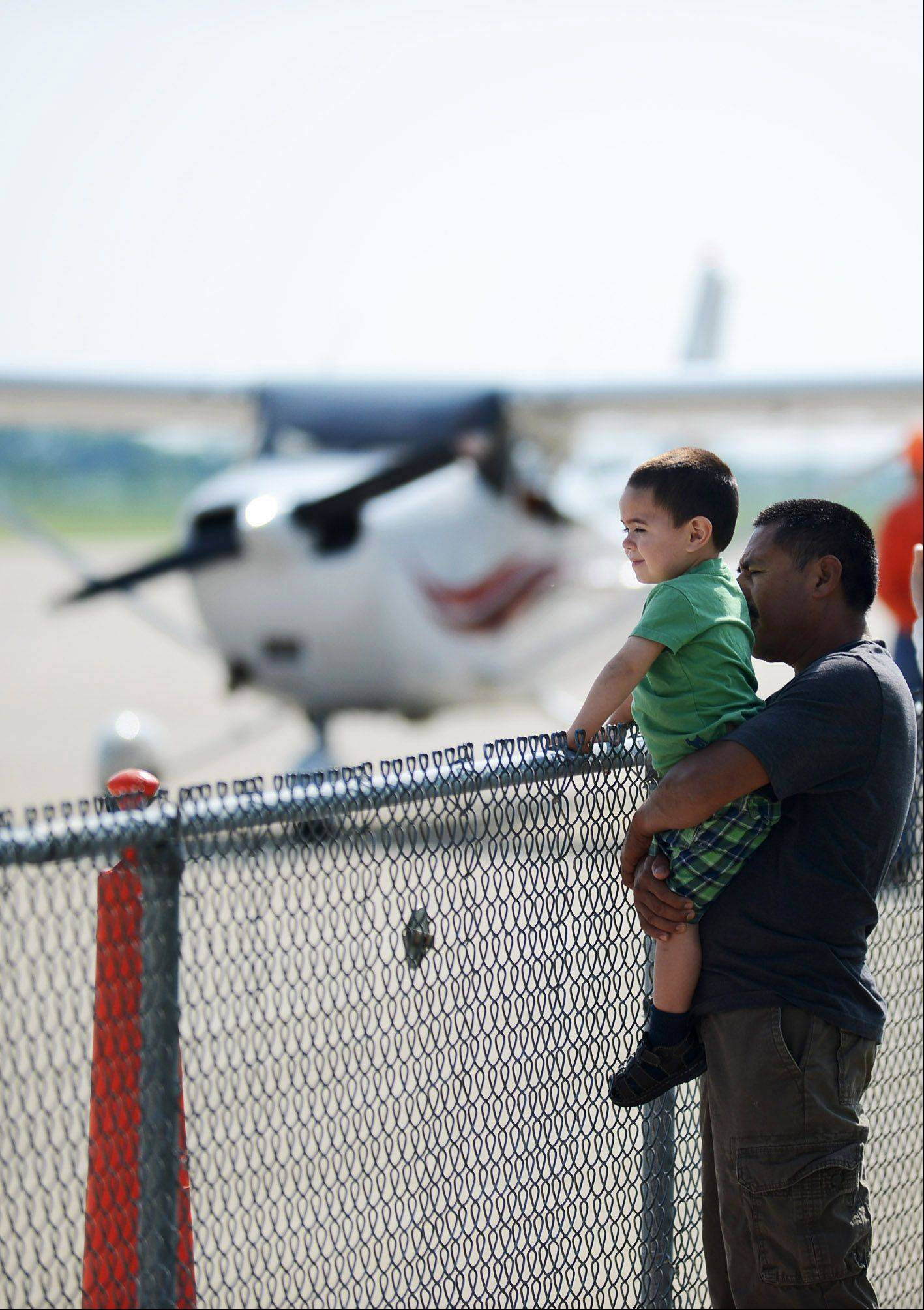 Santiago Landeros and his son, Santiago Jr., of Sugar Grove, check out the airplanes during the Young Eagles event Sunday at the Aurora Municipal Airport.