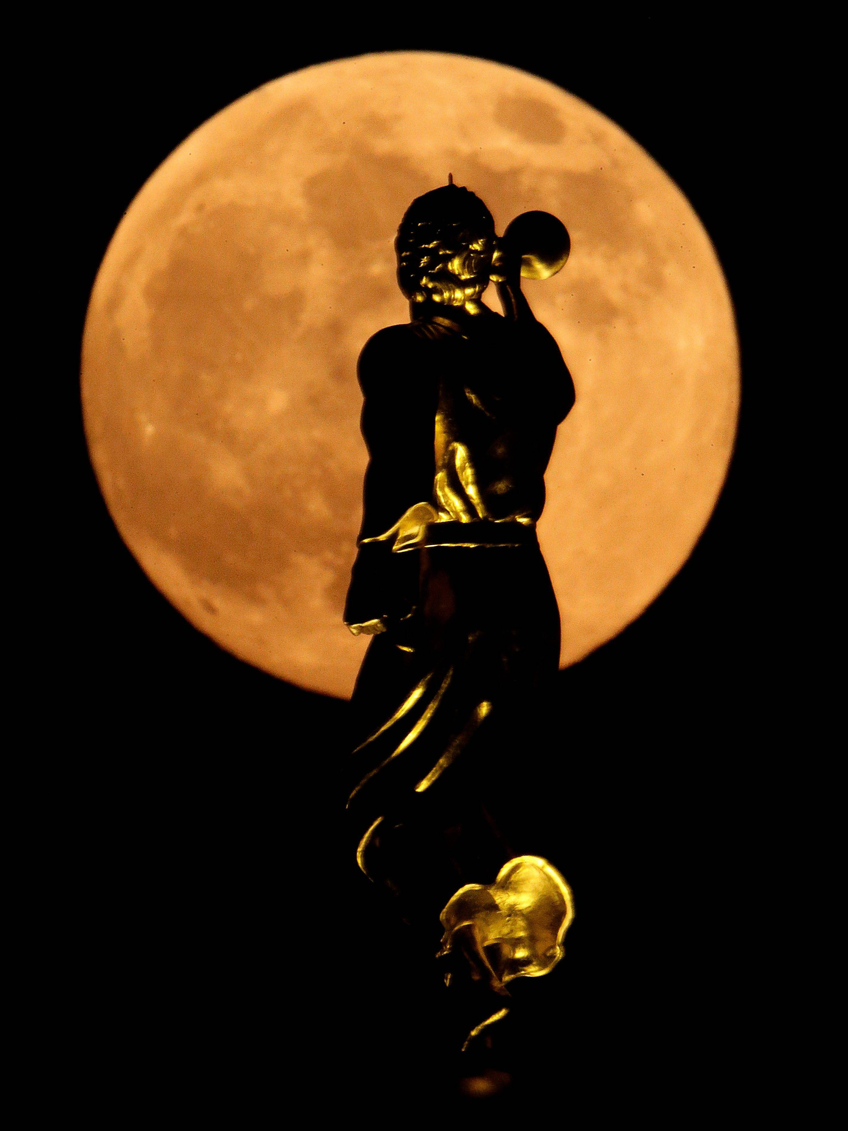 A statue of the Angel Moroni on top a Latter-day Saints temple is silhouetted against the rising moon Saturday, June 22, 2013, in Kansas City, Mo. The moon, which will reach its full stage on Sunday, is expected to be 13.5 percent closer to earth during a phenomenon known as supermoon.