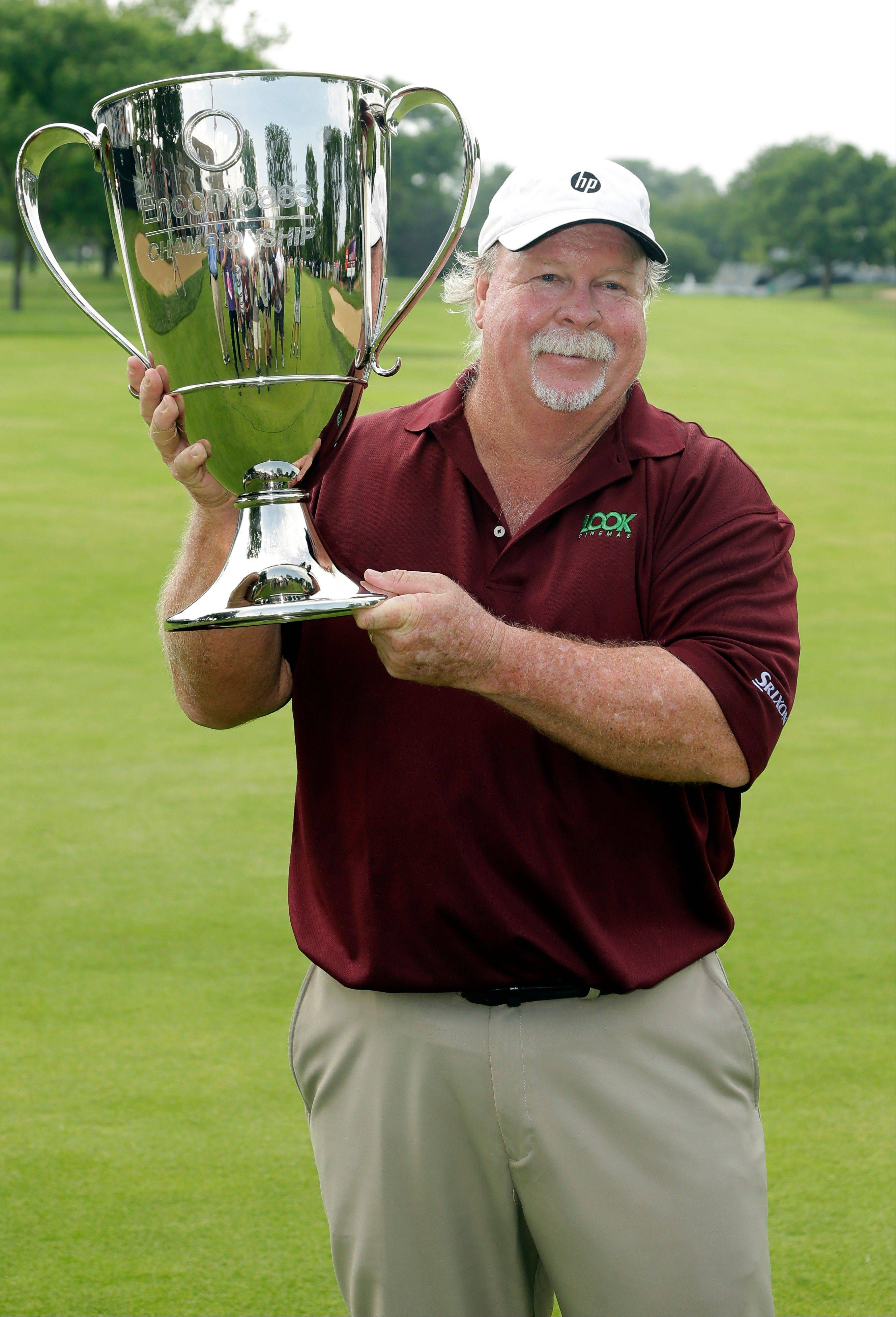 Craig Stadler displays his trophy after winning the Champions Tour's Encompass Championship on Sunday at North Shore Country Club in Glenview.