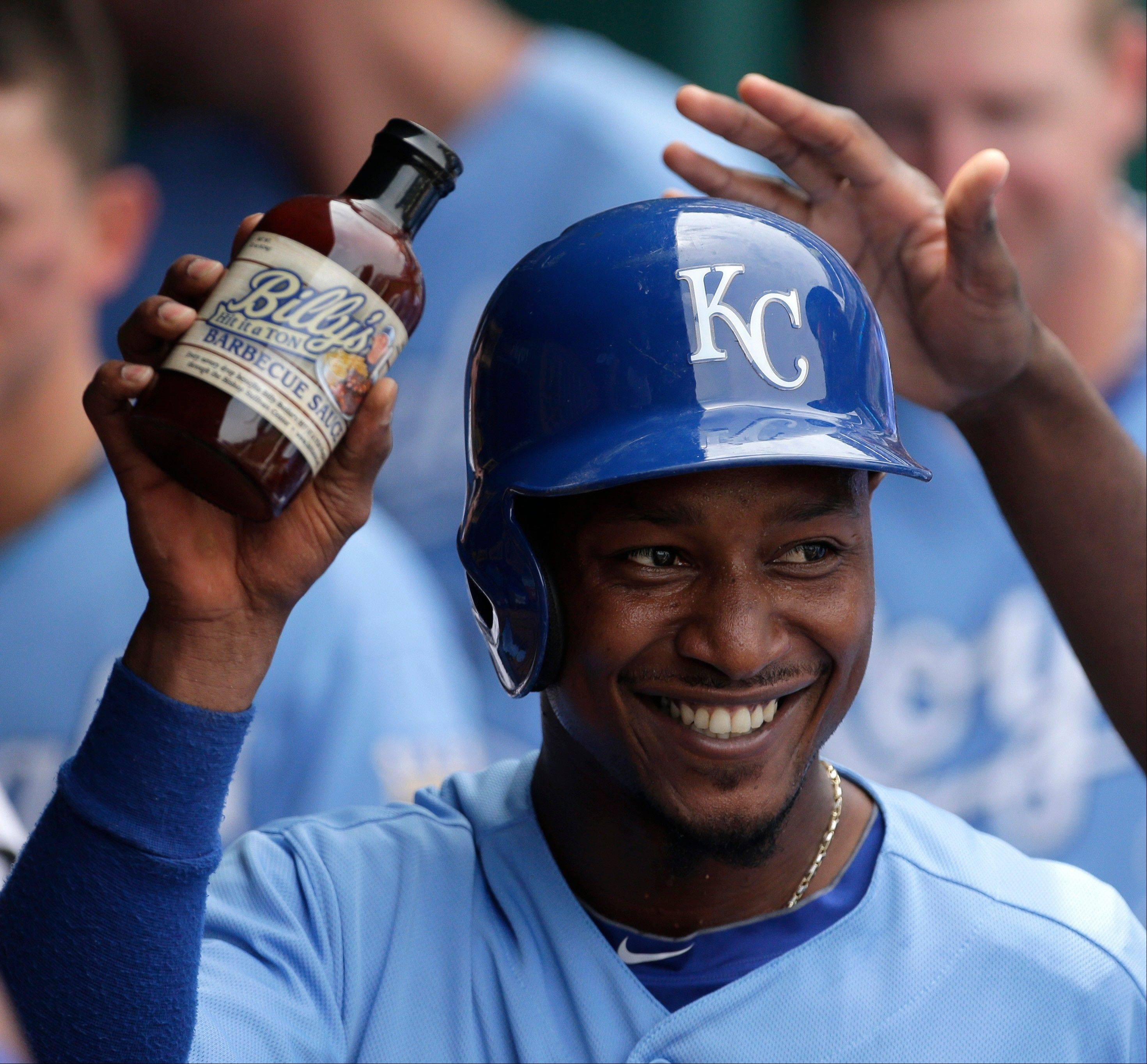 The Kansas City Royals' Jarrod Dyson celebrates in the dugout with a jar of Billy's barbeque sauce after scoring on a single by Alex Gordon during the third inning of a baseball game against the Chicago White Sox, Sunday, June 23, 2013, in Kansas City, Mo.