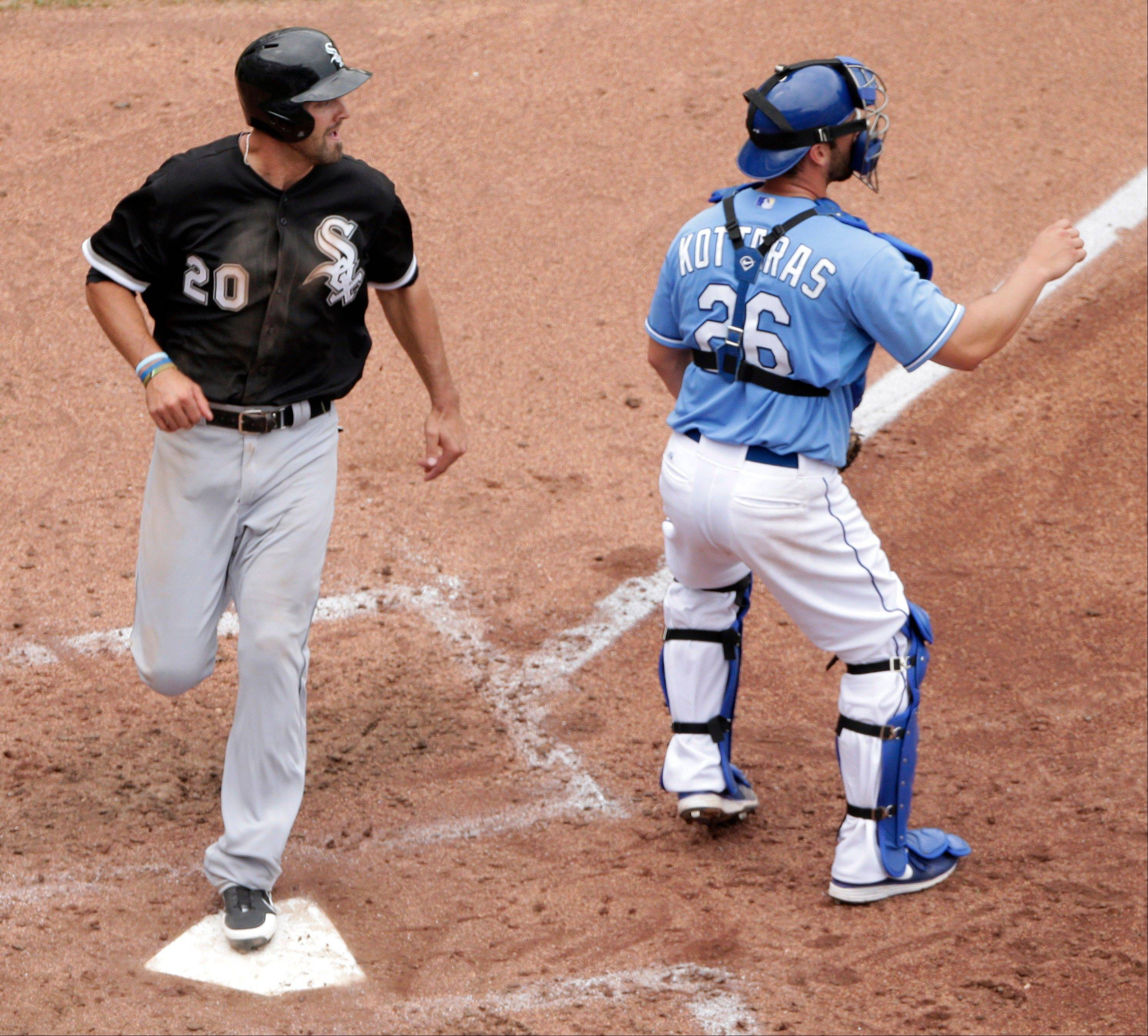 The Chicago White Sox' Jordan Danks runs past Kansas City Royals catcher George Kottaras to score on a double by Gordon Beckham during the seventh inning of a baseball game, Sunday, June 23, 2013, in Kansas City, Mo.