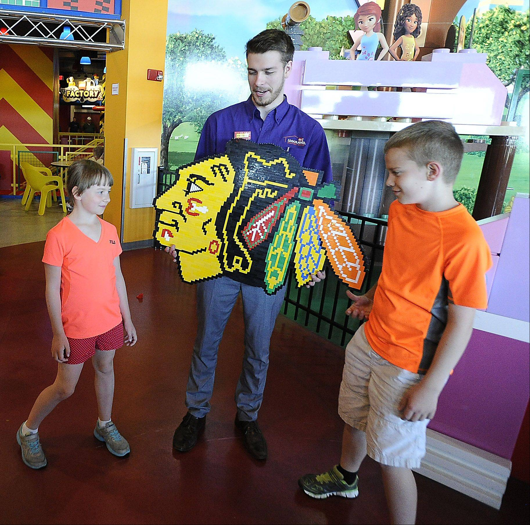 Andrew Johnson of Bartlett shows David, 10, and Gabija, 7, Fedaravicius of Streamwood the Chicago Blackhawks logo he made using 756 Lego pieces. The design, which Johnson built in about a week, was on display Monday at Legoland Discovery Center in Schaumburg.