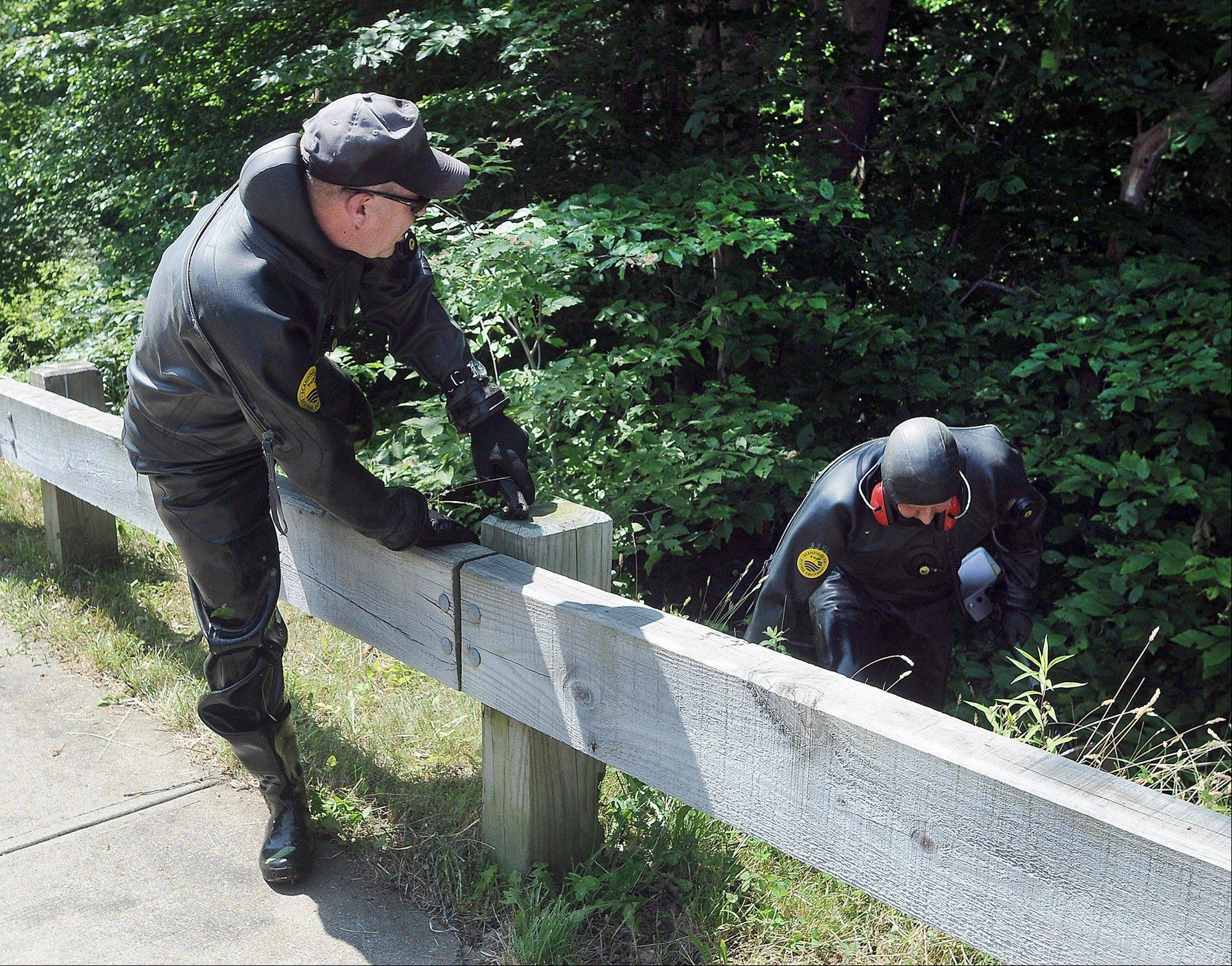 Law enforcement officers wearing wet suits emerge from bushes Monday during a search for evidence along a road near the home of New England Patriots tight end Aaron Hernandez in North Attleborough, Mass. The body of Odin Lloyd, a 27-year-old semipro football player for the Boston Bandits, was found in a nearby industrial park on June 17.