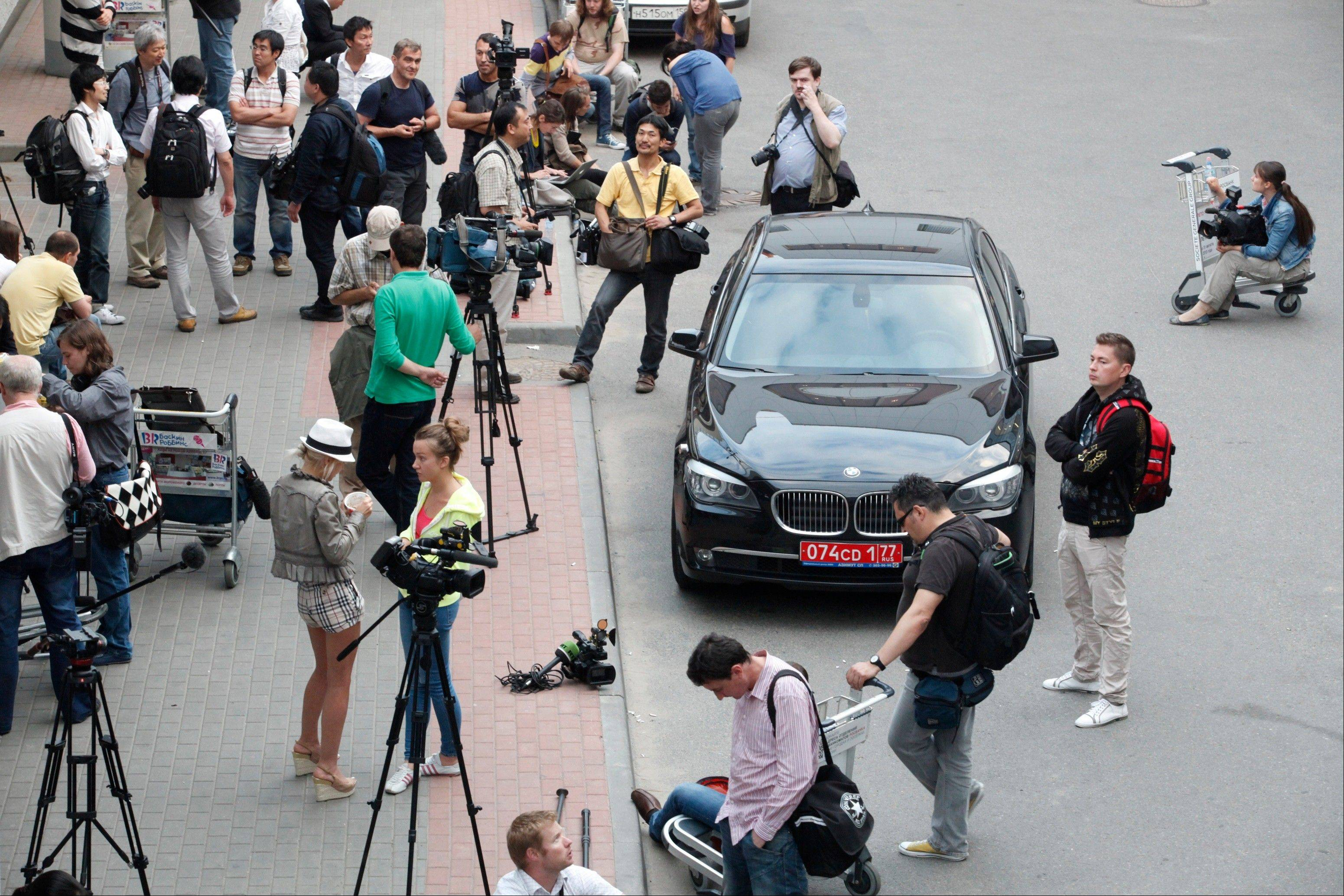 Journalists stand next to Ecuador�s Ambassador�s car while waiting for the arrival of Edward Snowden, a former CIA employee who recently leaked top-secret documents about sweeping U.S. surveillance programs, at Sheremetyevo airport, just outside Moscow, Russia, Sunday,