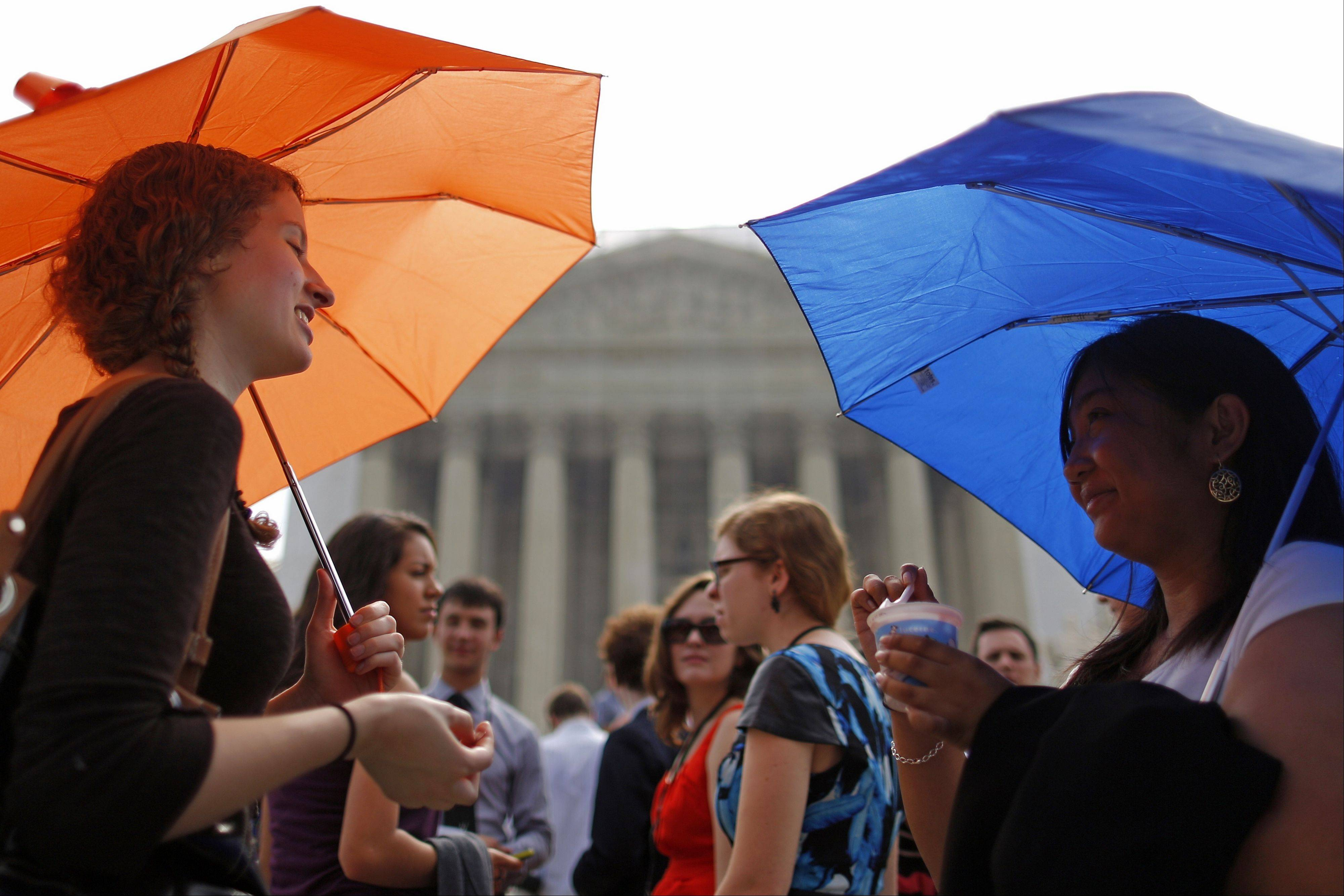 Livia Maas, left, and Khrystan Policarpio, both from Berkeley, Calif., stand under umbrellas to shield themselves from the sun in front of the Supreme Court in Washington Monday, as they queue for the court's session.