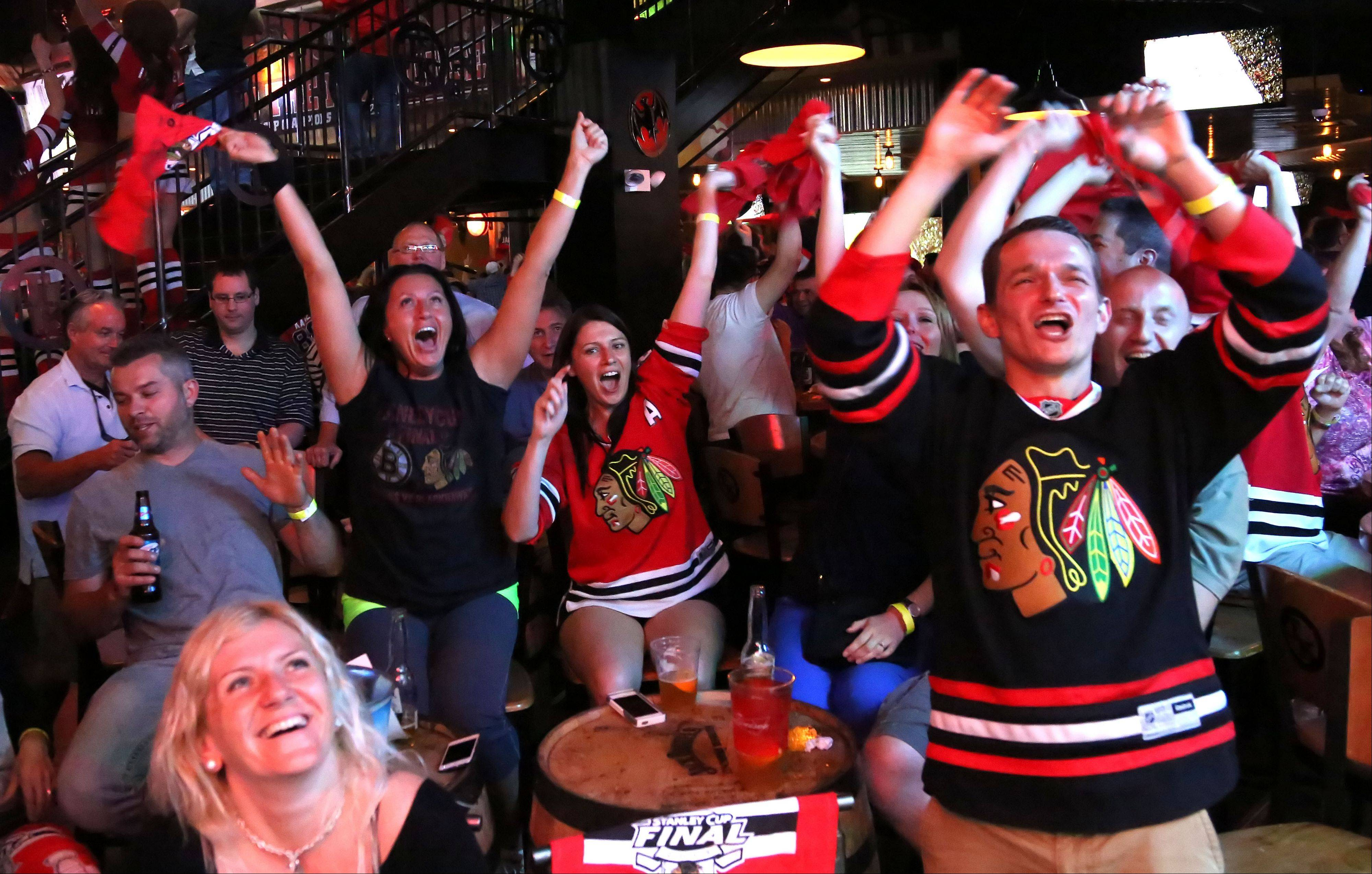 Hawks fans react after Jonathan Toews' goal in the second period as people packed into Toby Keith's I Love This Bar to watch Game 6 of the Stanley Cup Finals Monday night in Rosemont.