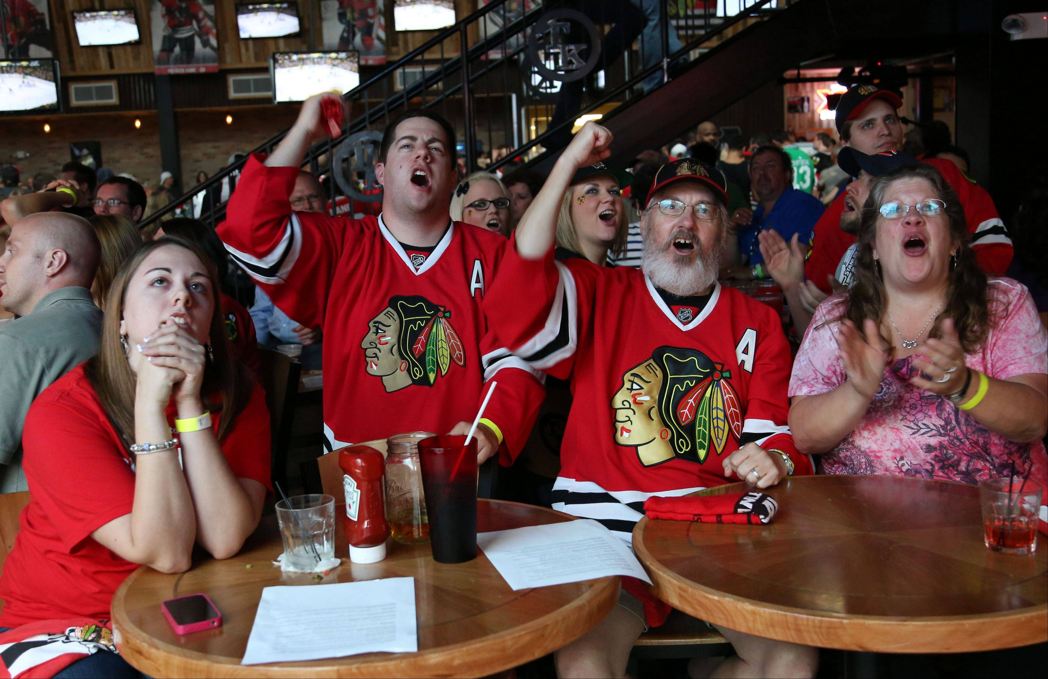 From left, Hayley McQuillan, Dan Leuze, Joe Leuze and Marilyn Leuze, all of Glendale Heights cheer as they watch game six of the Stanley Cup Finals at Toby Keith's I Love This Bar in Rosemont Monday night.