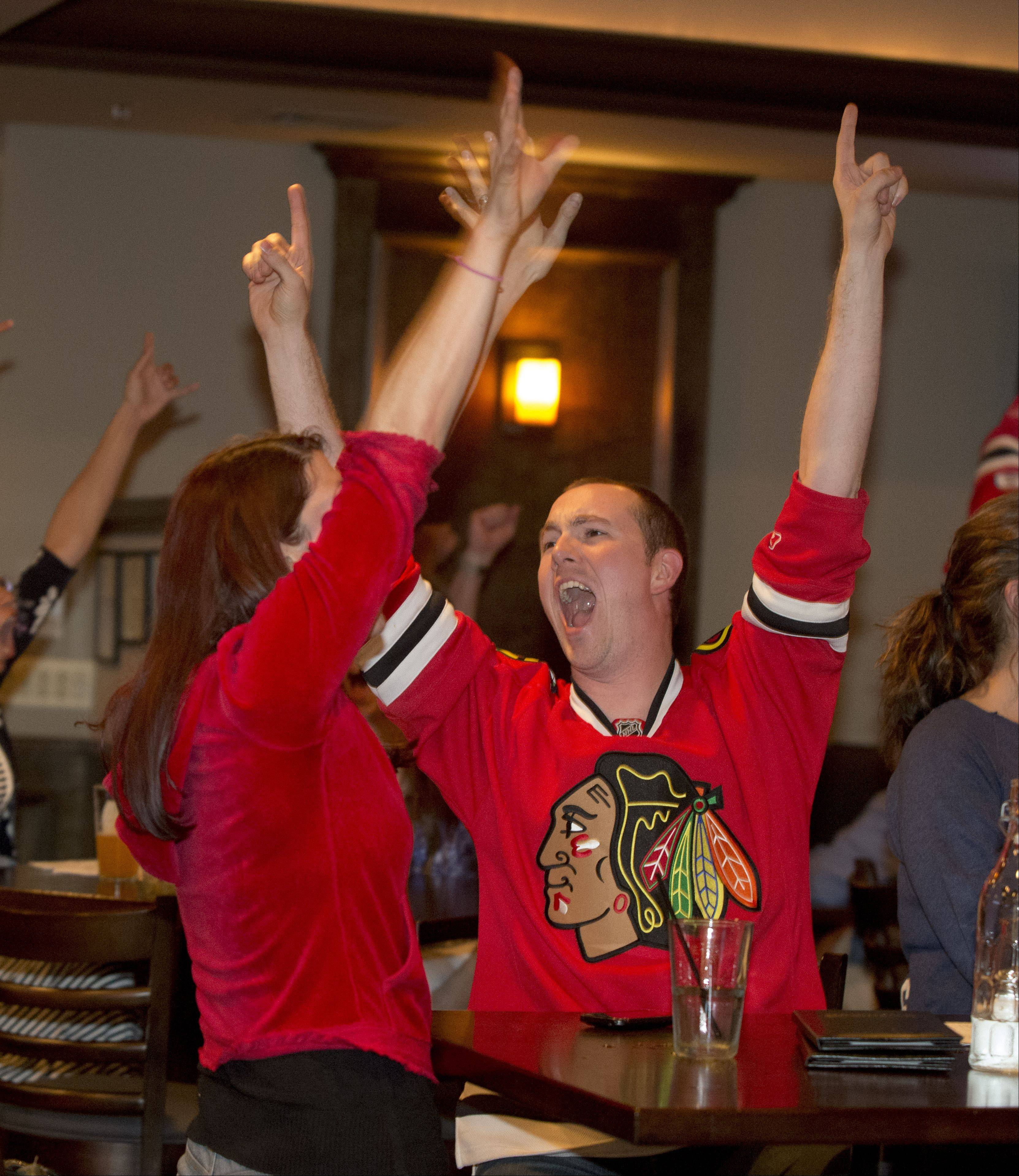 "Chicago Blackhawks fans Katie and Joe Handy of Aurora cheer the Blackhawks winning goal while watch their team win the Stanley Cup at Warren's Ale House in Wheaton, Monday. Joe Handy said ""It is great to have the cup back in Chicago"""