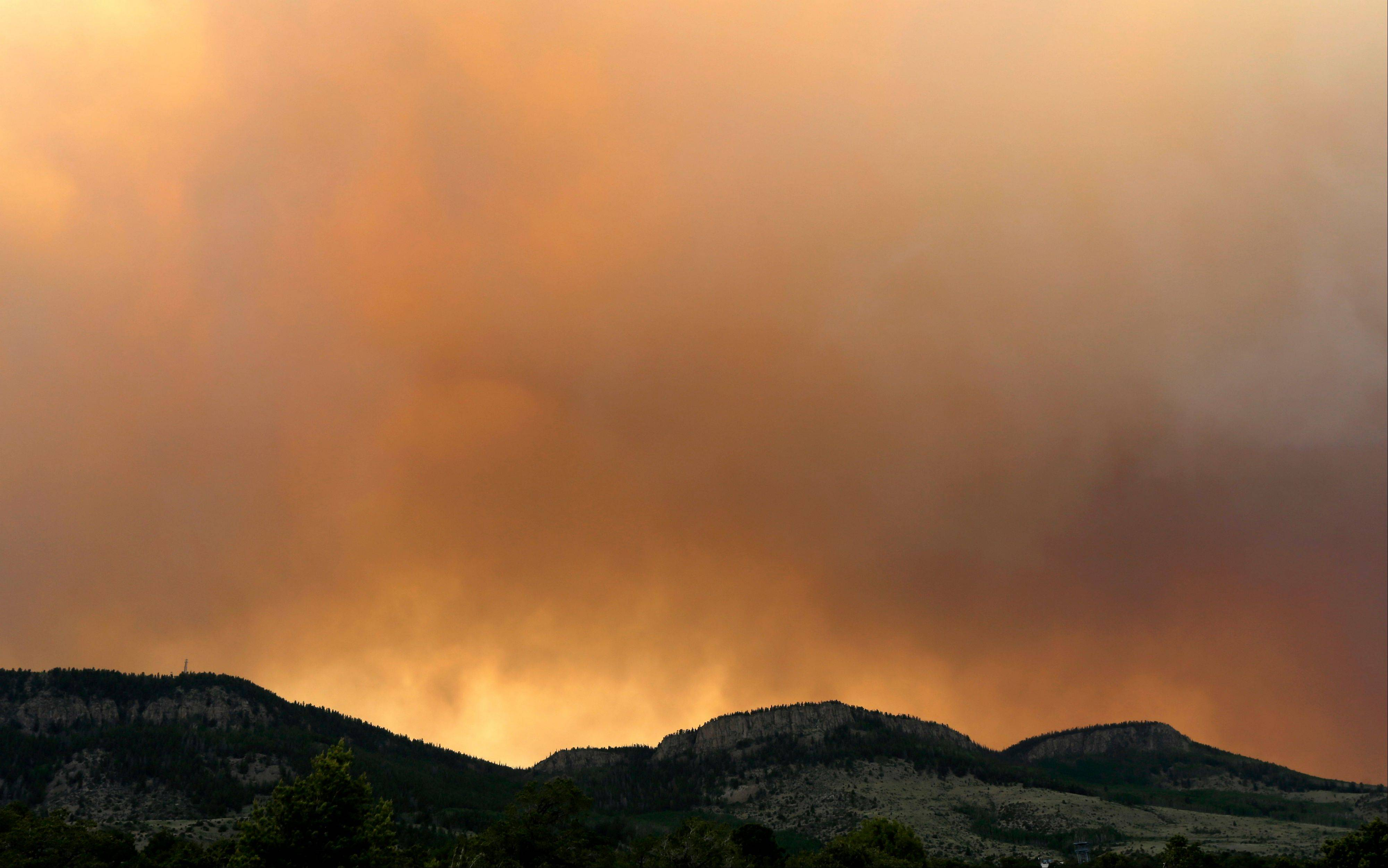 Wildfire smoke blankets a ridge Sunday near Alpine, Colo. A large wildfire near South Fork, a popular summer retreat in southern Colorado, continues to be driven by winds and fueled by dead trees in a drought-stricken area, authorities said Sunday.