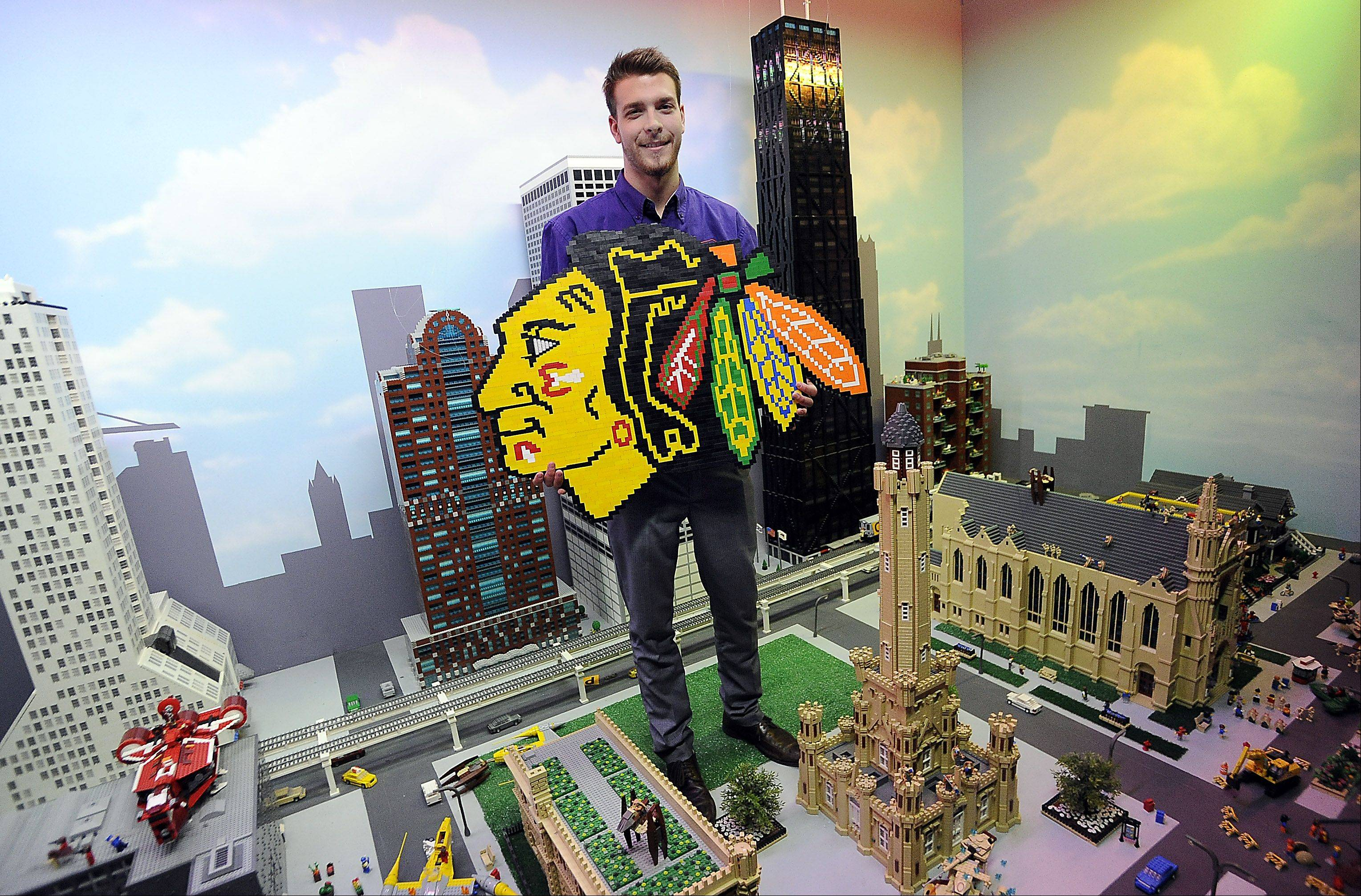 Andrew Johnson of Bartlett holds the Blackhawks logo he made using 756 Lego pieces above a downtown Chicago landscape also made of Lego pieces.