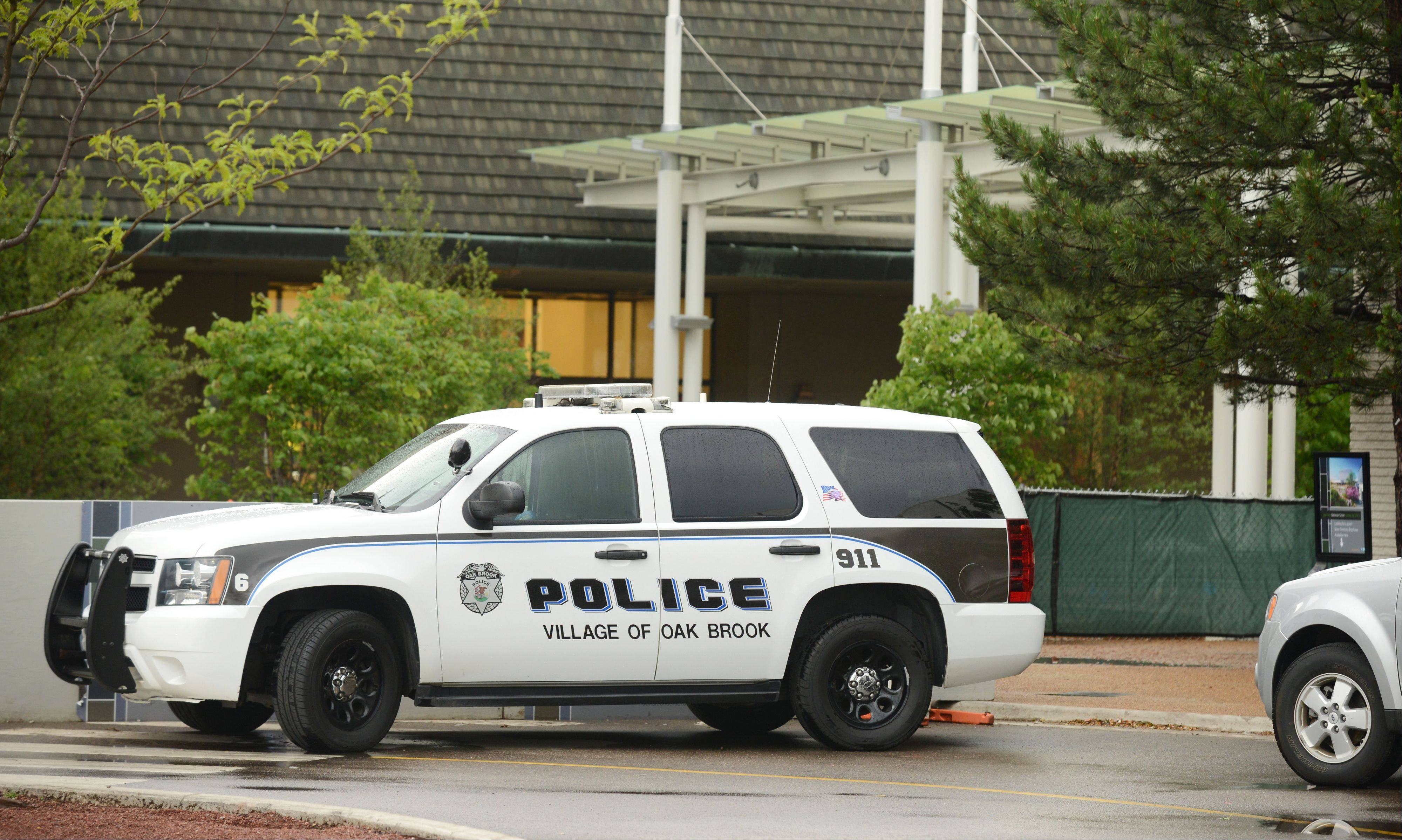 An Oak Brook police vehicle sits near one of the entrances to Oakbrook Center mall after a shooting Sunday at the C.D. Peacock jewelry store.