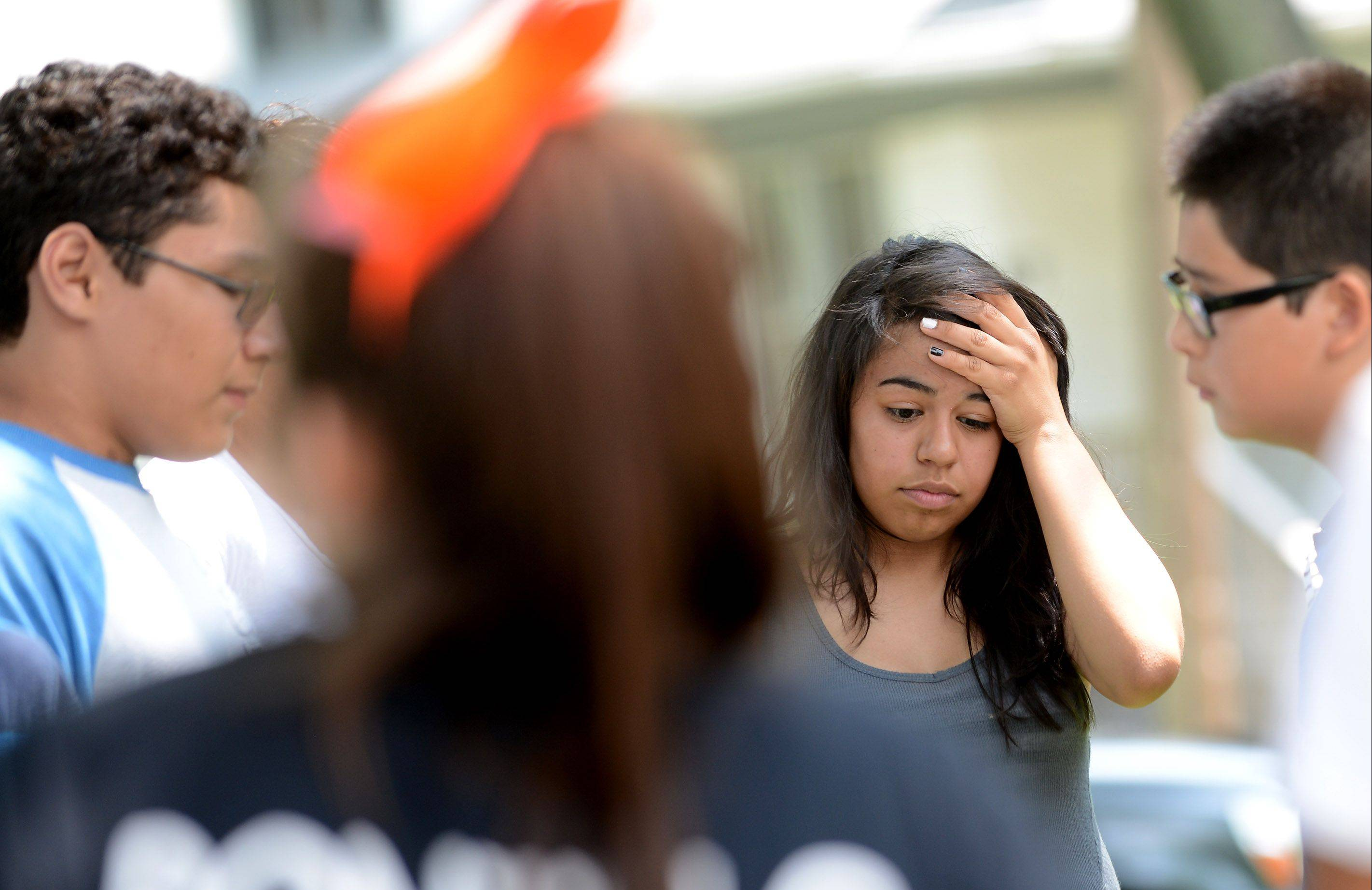Daniela Mendoza, 13, of Elgin and other former and current students gather for a memorial Monday outside the home of Martin Powers, a teacher at Kimball Middle School who died at age 50.
